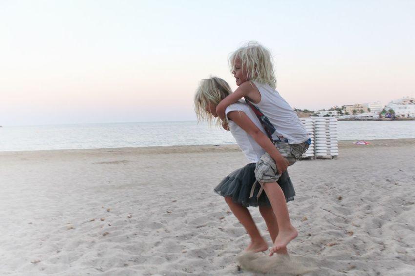 Piggyback on the beach Piggyback Beach Friends Siblings Holiday Fun Happiness Childhood Sea Sundown Sunset Pastel
