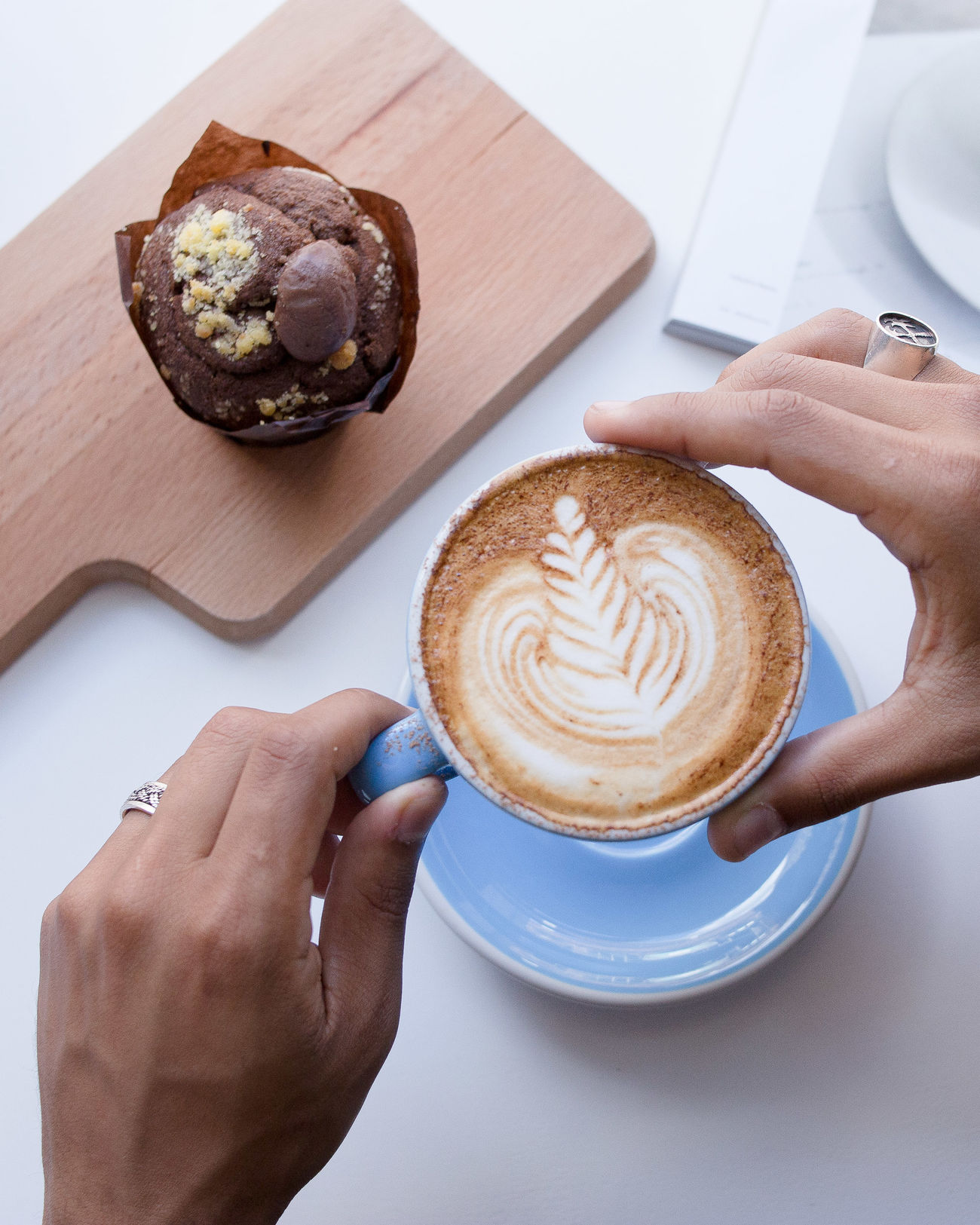 Cappuccino Close-up Coffee - Drink Coffee Cup Day Drink Food And Drink Freshness Froth Art Frothy Drink Holding Human Body Part Human Hand Indoors  Latte Latte Muffin One Person Ready-to-eat Real People Refreshment Saucer Table White Background Women