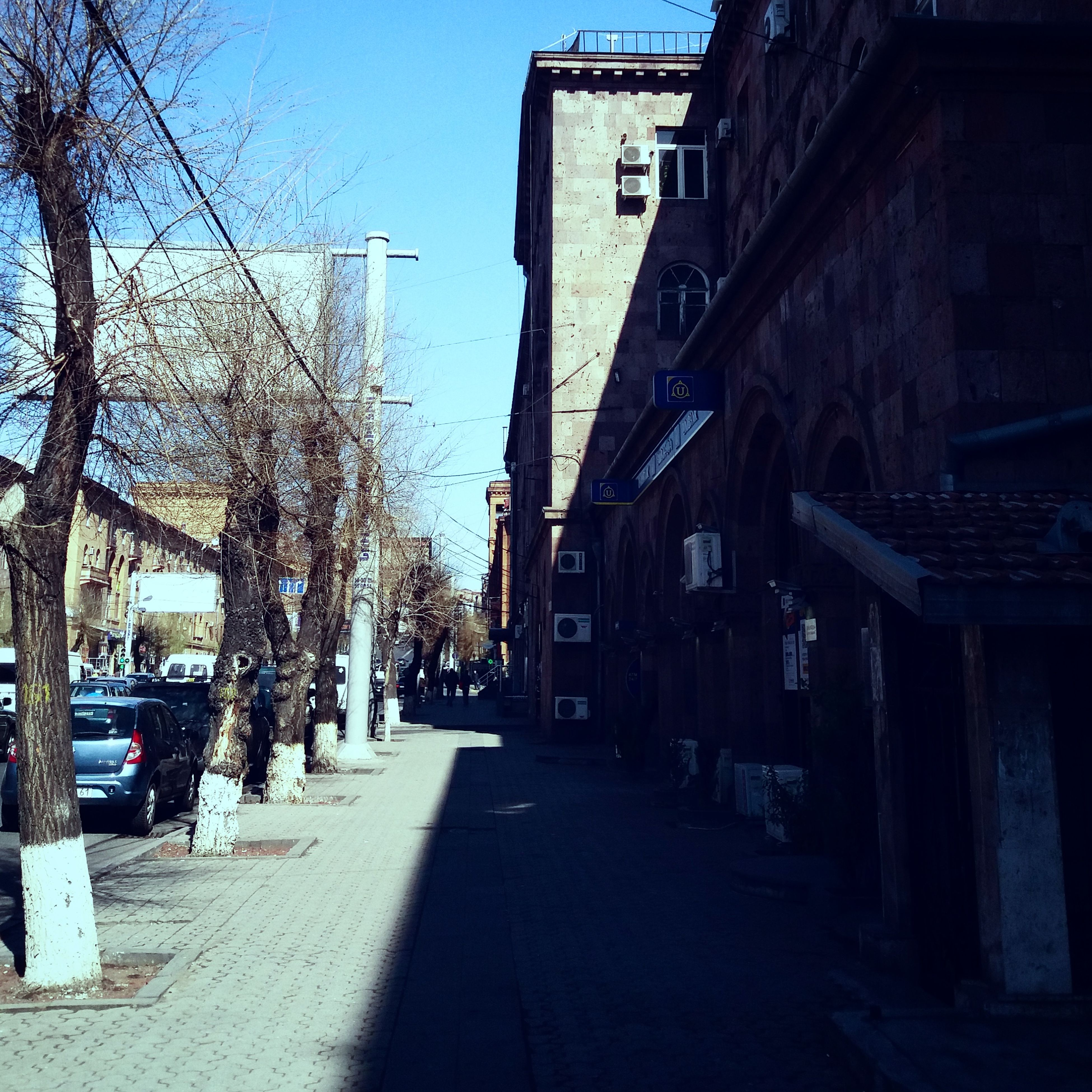 building exterior, the way forward, architecture, built structure, diminishing perspective, street, city, clear sky, vanishing point, tree, sunlight, narrow, long, residential structure, shadow, residential building, empty, cobblestone, walkway, road