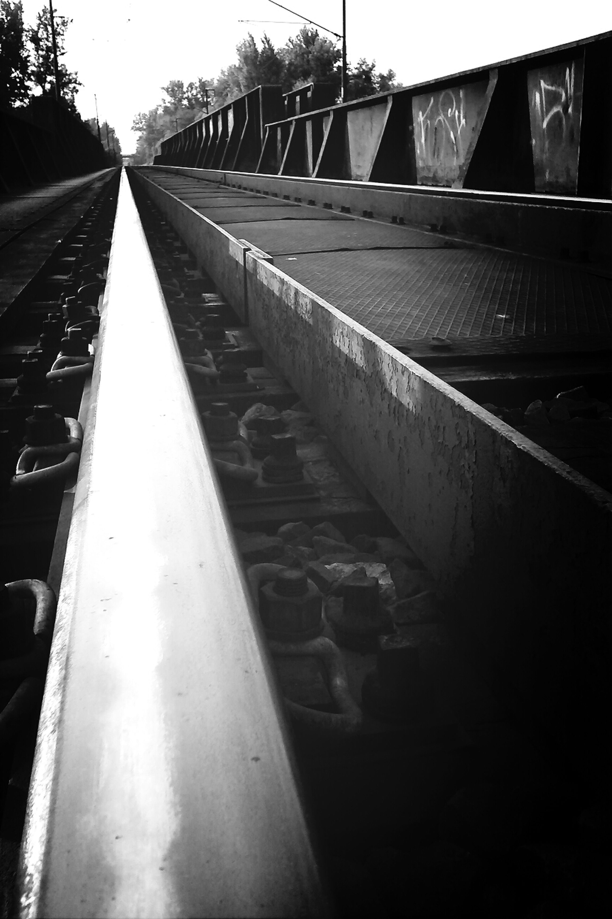 transportation, diminishing perspective, the way forward, vanishing point, built structure, architecture, connection, metal, railroad track, sky, bridge - man made structure, outdoors, rail transportation, engineering, day, no people, travel, long, building exterior, metallic