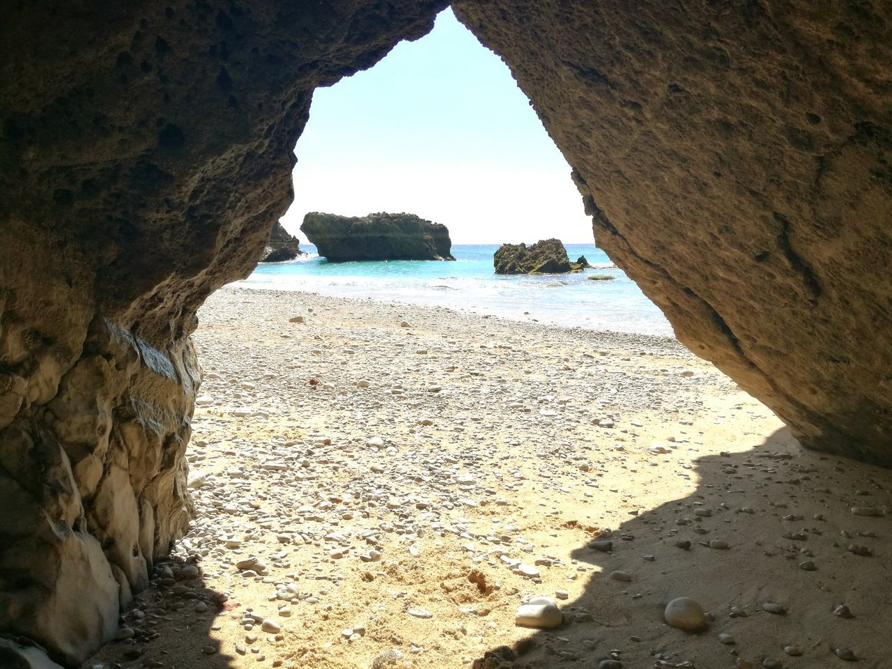 rock formation, rock - object, nature, sand, beauty in nature, beach, day, sea, scenics, sunlight, natural arch, tranquility, shadow, tranquil scene, outdoors, physical geography, no people, cliff, water, sky