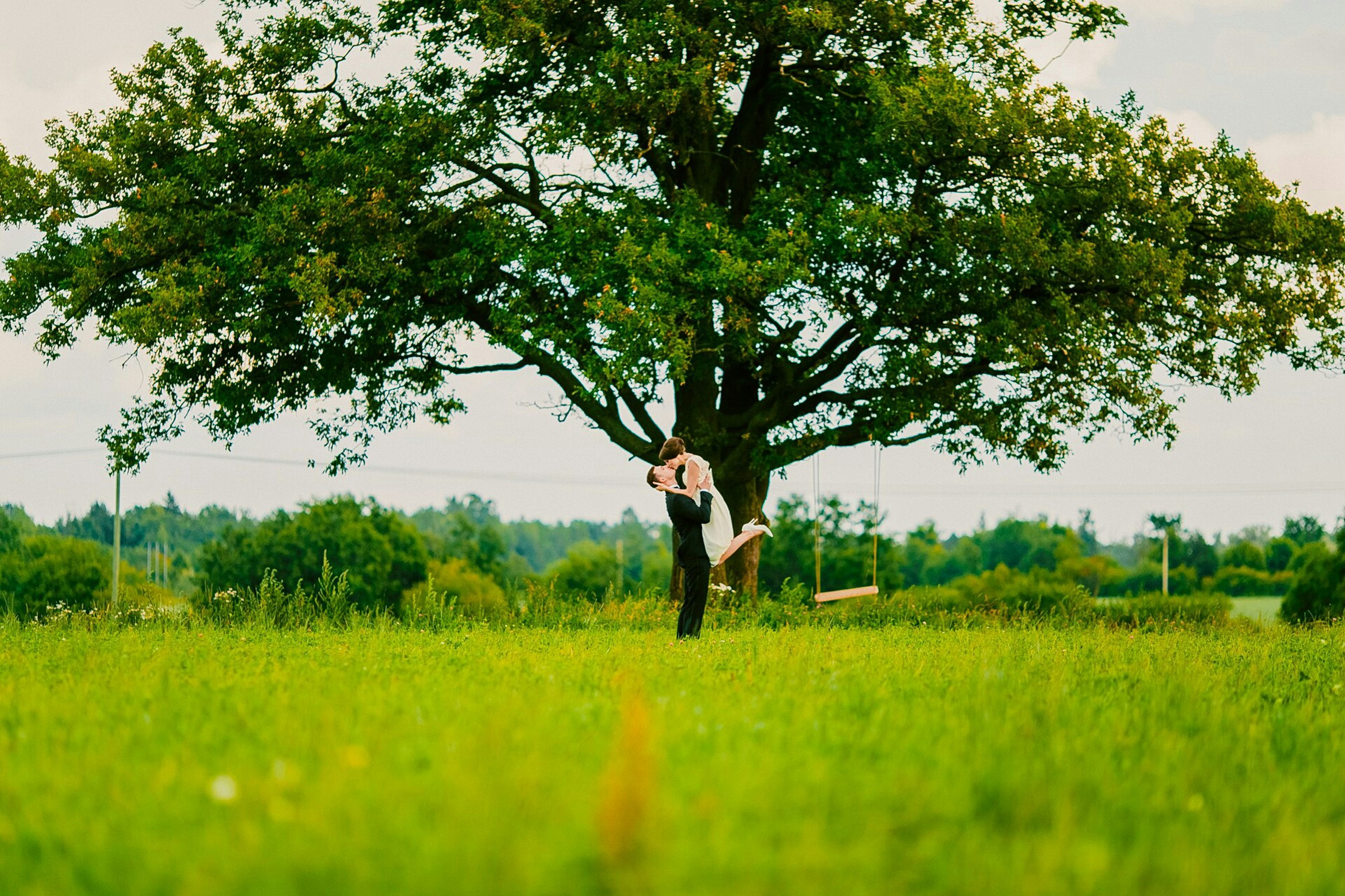 grass, field, lifestyles, full length, tree, grassy, green color, leisure activity, growth, standing, casual clothing, landscape, nature, tranquility, sky, tranquil scene, plant, young adult