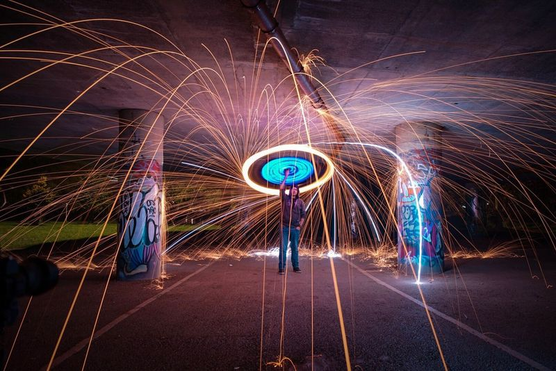 Long Exposure Night Illuminated Wire Wool Light Painting Motion One Person Light Trail Standing Men Arts Culture And Entertainment People Full Length Outdoors Adult Adults Only One Man Only Only Men Sky