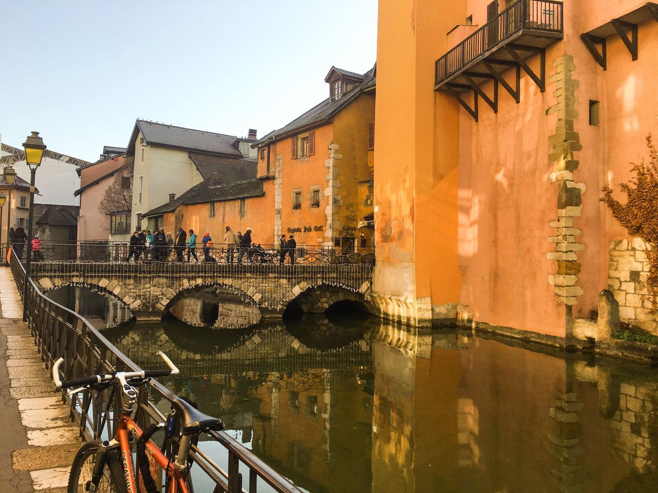 architecture, building exterior, built structure, bicycle, canal, outdoors, day, large group of people, real people, transportation, water, city, men, sky, people