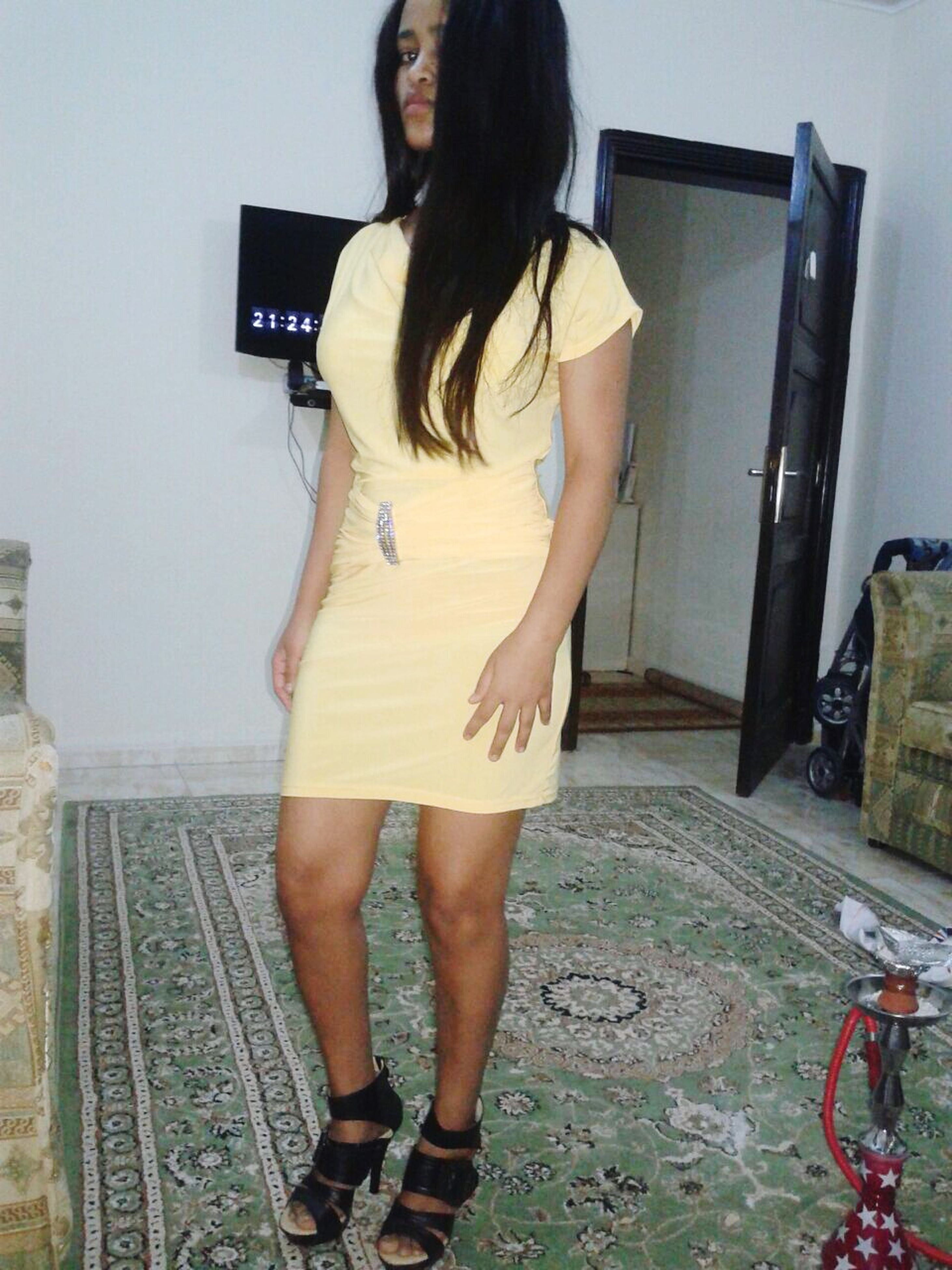 lifestyles, standing, full length, young adult, young women, casual clothing, leisure activity, long hair, front view, person, dress, holding, wall - building feature, three quarter length, side view, sensuality