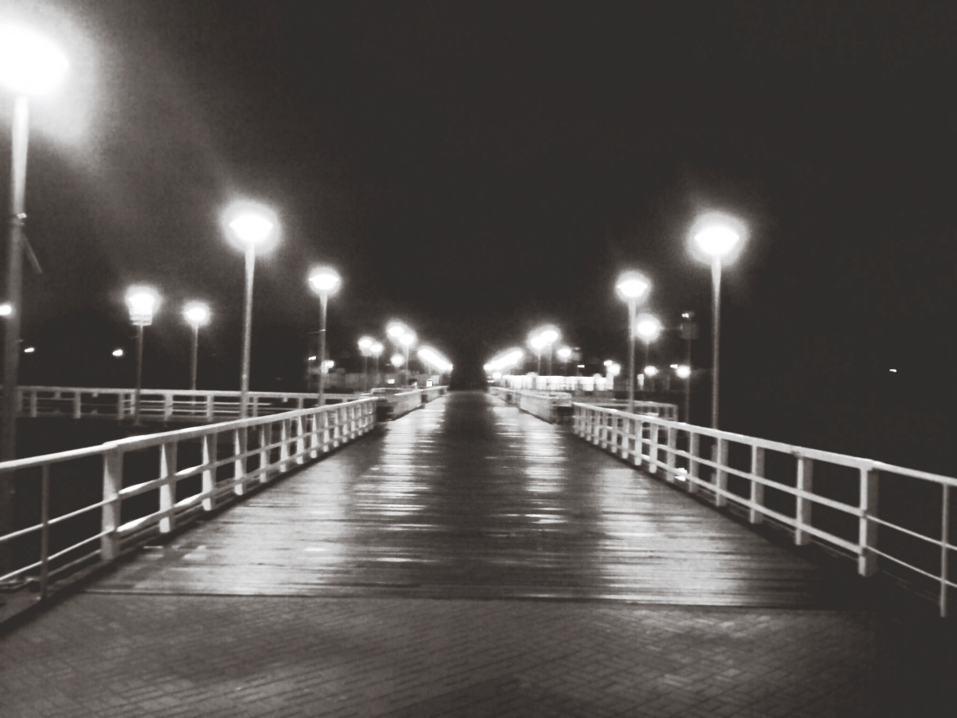 illuminated, night, the way forward, street light, lighting equipment, built structure, railing, architecture, diminishing perspective, connection, vanishing point, bridge - man made structure, footbridge, reflection, walkway, in a row, empty, city, long, electric light