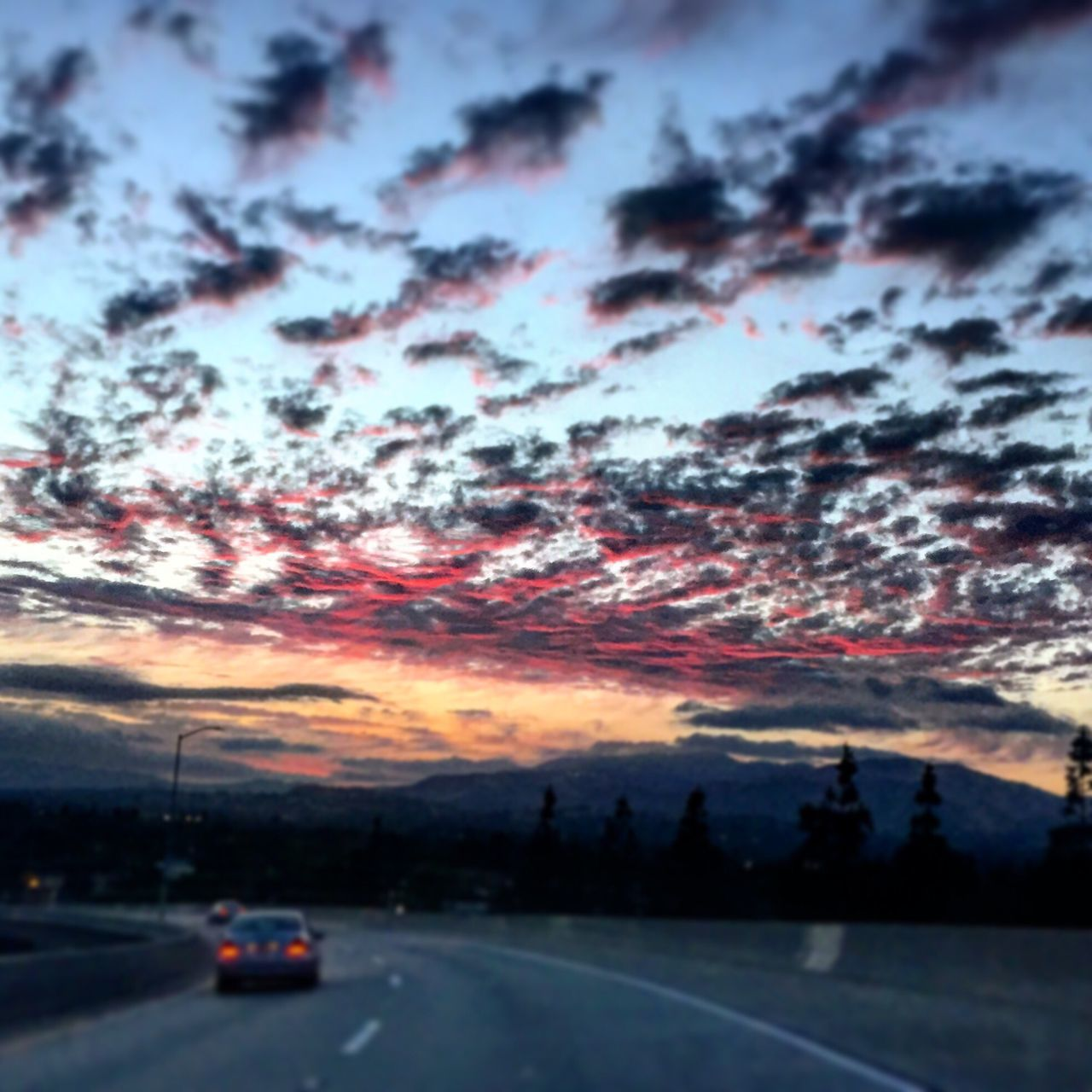 sunset, car, transportation, dramatic sky, cloud - sky, sky, scenics, beauty in nature, nature, no people, tranquil scene, road, tranquility, land vehicle, tree, outdoors, mountain, day