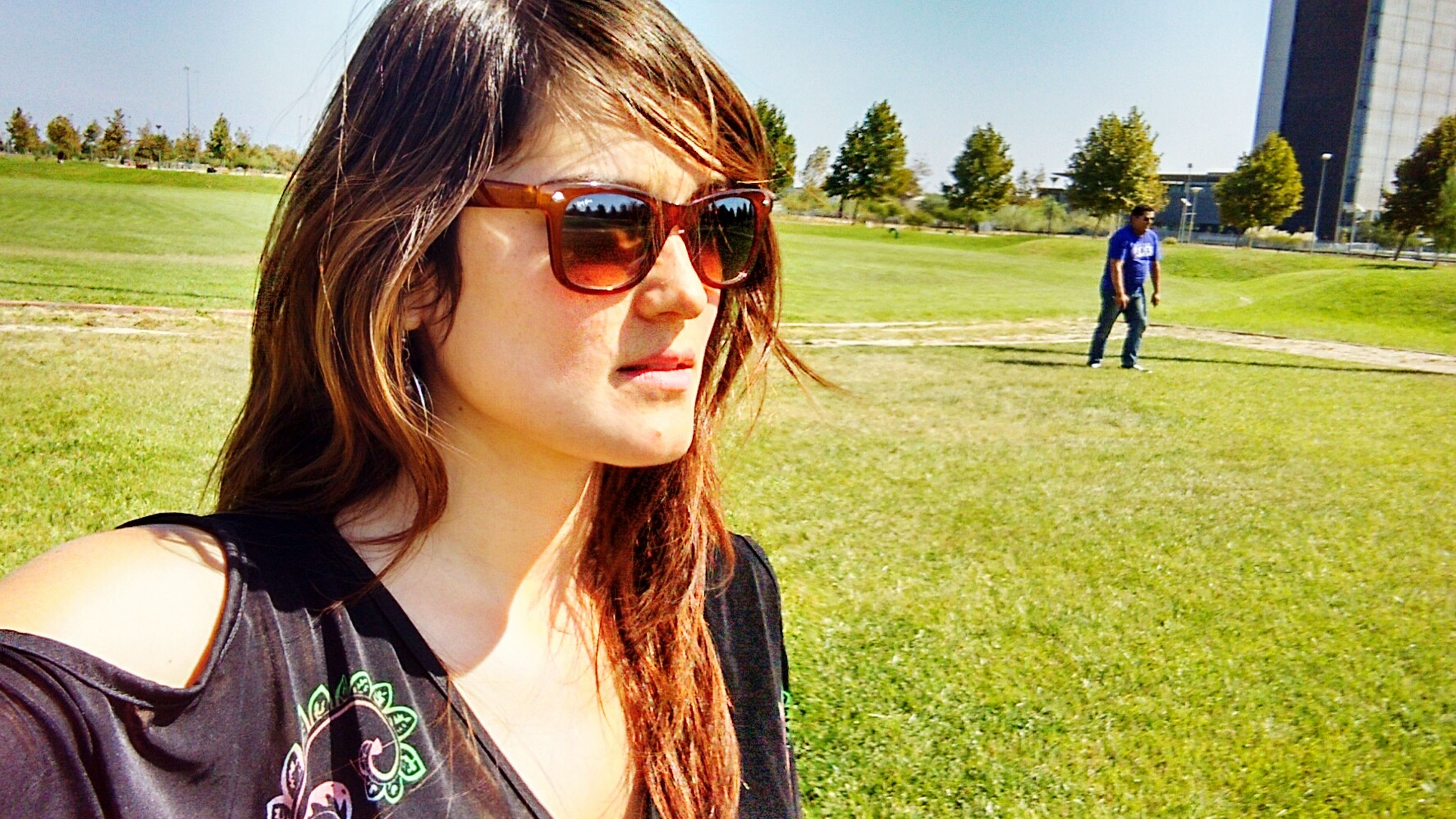 grass, person, lifestyles, leisure activity, young adult, looking at camera, portrait, young women, sunglasses, front view, sunlight, smiling, casual clothing, field, lawn, day, grassy, park - man made space