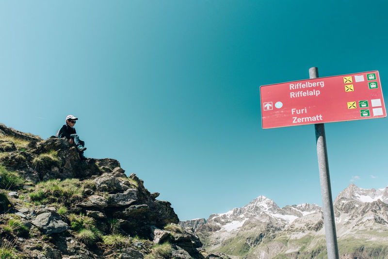 Lifestyle Travel Adventure Backpack Blue Boy Clear Sky Healthy Lifestyle Hiking Low Angle View Mountain Mountain Range Nature One Person Outdoors People Real People Red Road Sign Rock - Object Scenics Sky