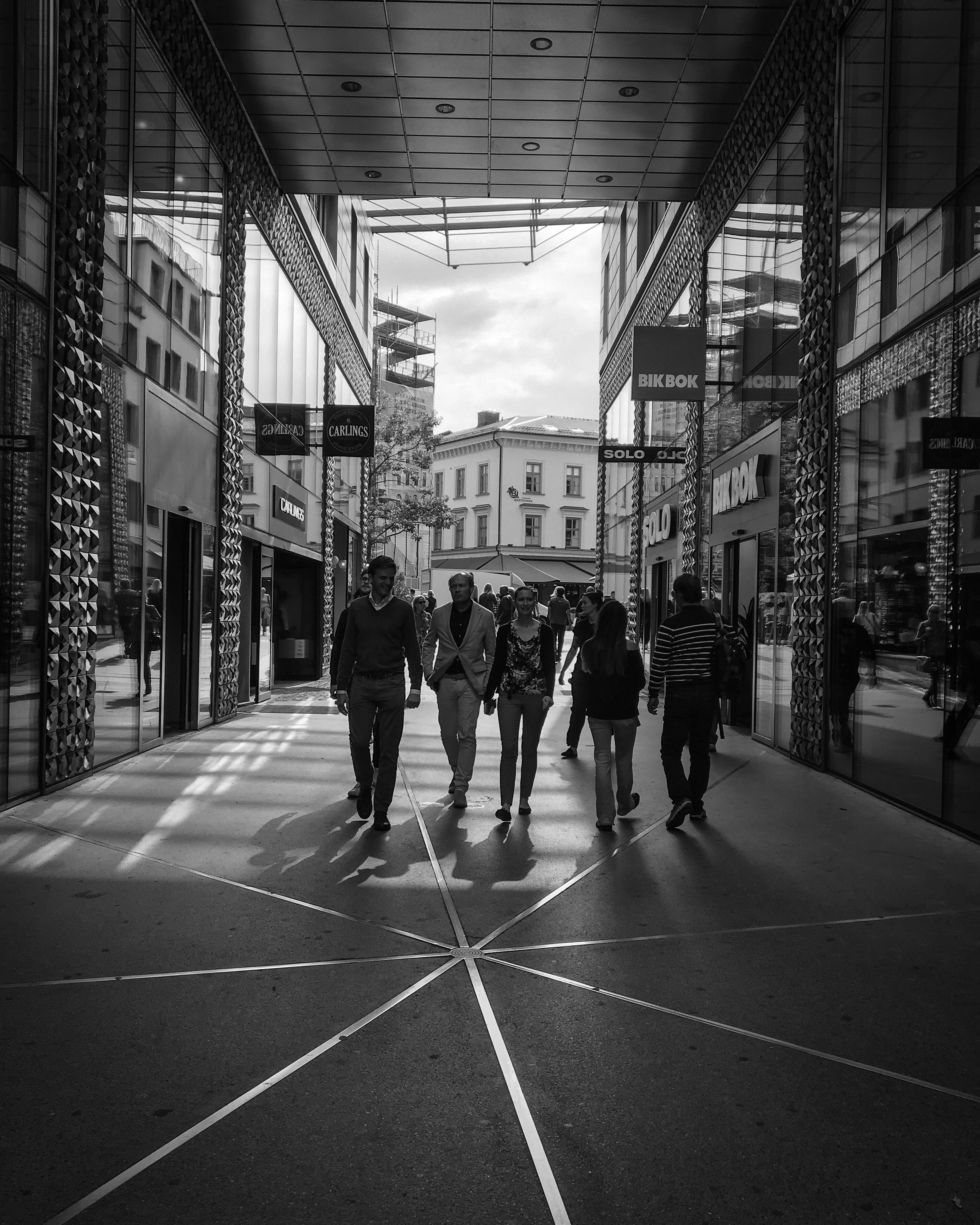 building exterior, architecture, built structure, men, walking, street, road marking, city, residential building, full length, road, rear view, person, city life, crossing, city street, casual clothing, day, outdoors, the way forward, sky