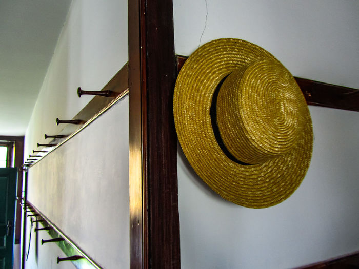 Solitary straw had on the wall of a shaker village wall lined with empty pegs for coast and hat symbolizes the decline of the shaker religious order. Hanging Out Hat Historical Building Massachusetts History Old Fashion Style Paint The Town Yellow Shakers Angles And Lines Architecture Built Structure Close-up Corner Corners And Edges Day Historical Place Illuminated Indoors  Low Angle View No People Shaker Village Straw Hat Close Up Wall - Building Feature