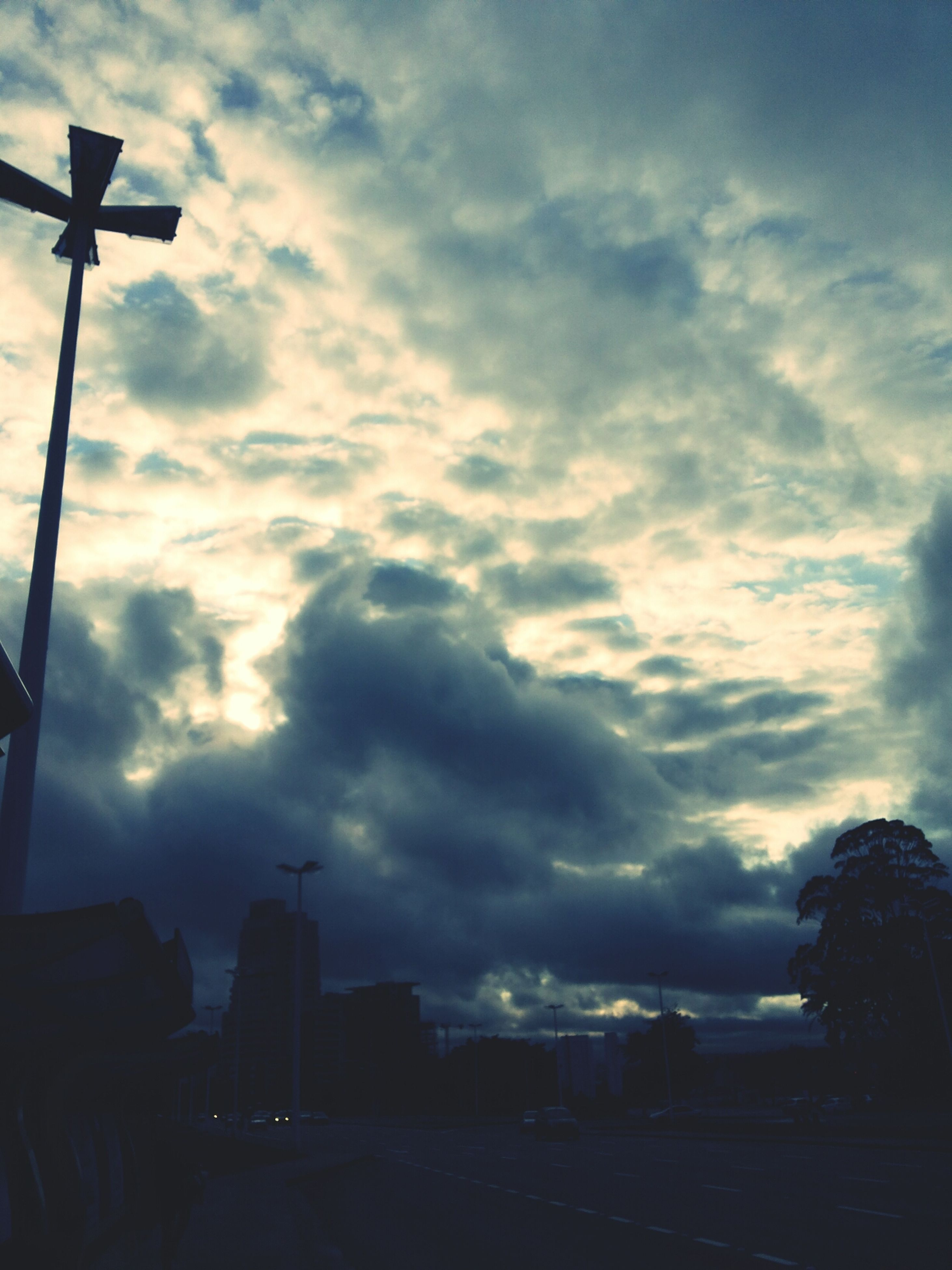 sky, cloud - sky, building exterior, silhouette, built structure, cloudy, architecture, cloud, sunset, transportation, street light, city, low angle view, weather, car, street, dusk, land vehicle, road, building