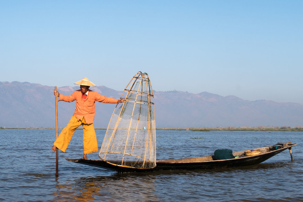 Balance Balancing Act Burma Day Fisherman Fishing Fishing Boat Fishing Tools Hat Inle Lake Lake Myanmar Nature Net Orange Clothes Outdoors People Sky Standing Tradition Traditional Clothing Water