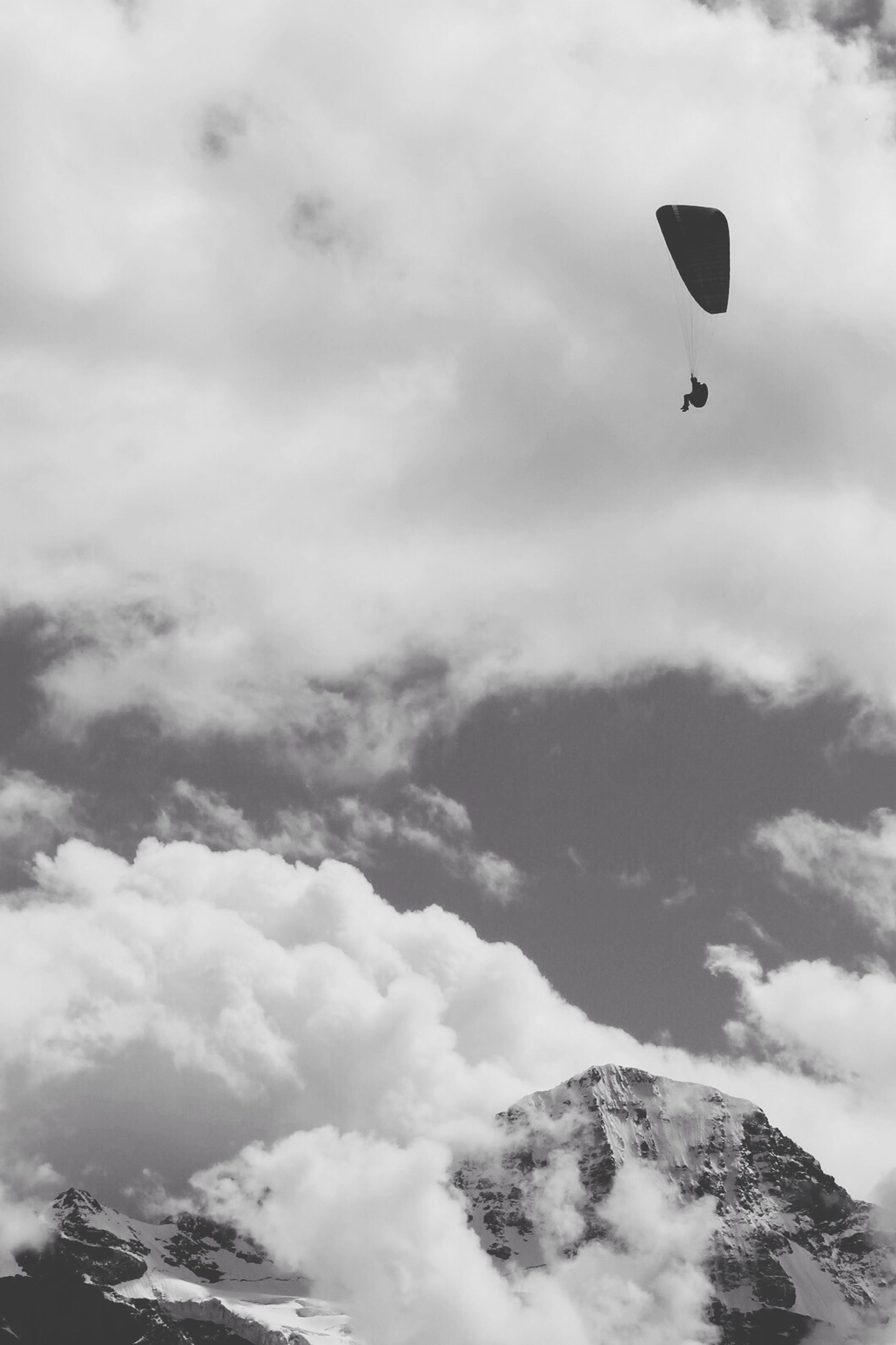 flying, sky, mid-air, low angle view, cloud - sky, parachute, paragliding, adventure, cloud, tranquility, extreme sports, one person, scenics, mountain, nature, unrecognizable person, leisure activity, beauty in nature, cloudy, transportation