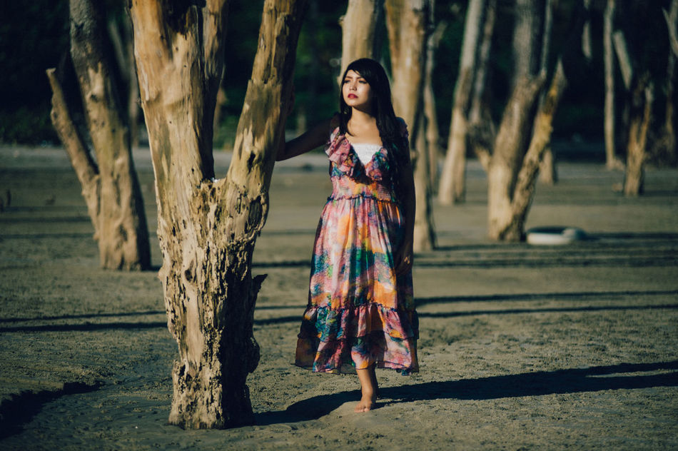 Adult Adults Only Beautiful Woman Beauty Black Hair Day Dress Fashion Fashion Model Focus On Foreground Forest Full Length Lifestyles Looking At Camera Nature One Person Only Women Outdoors Portrait Real People Sunlight Tree Tree Trunk Young Adult Young Women