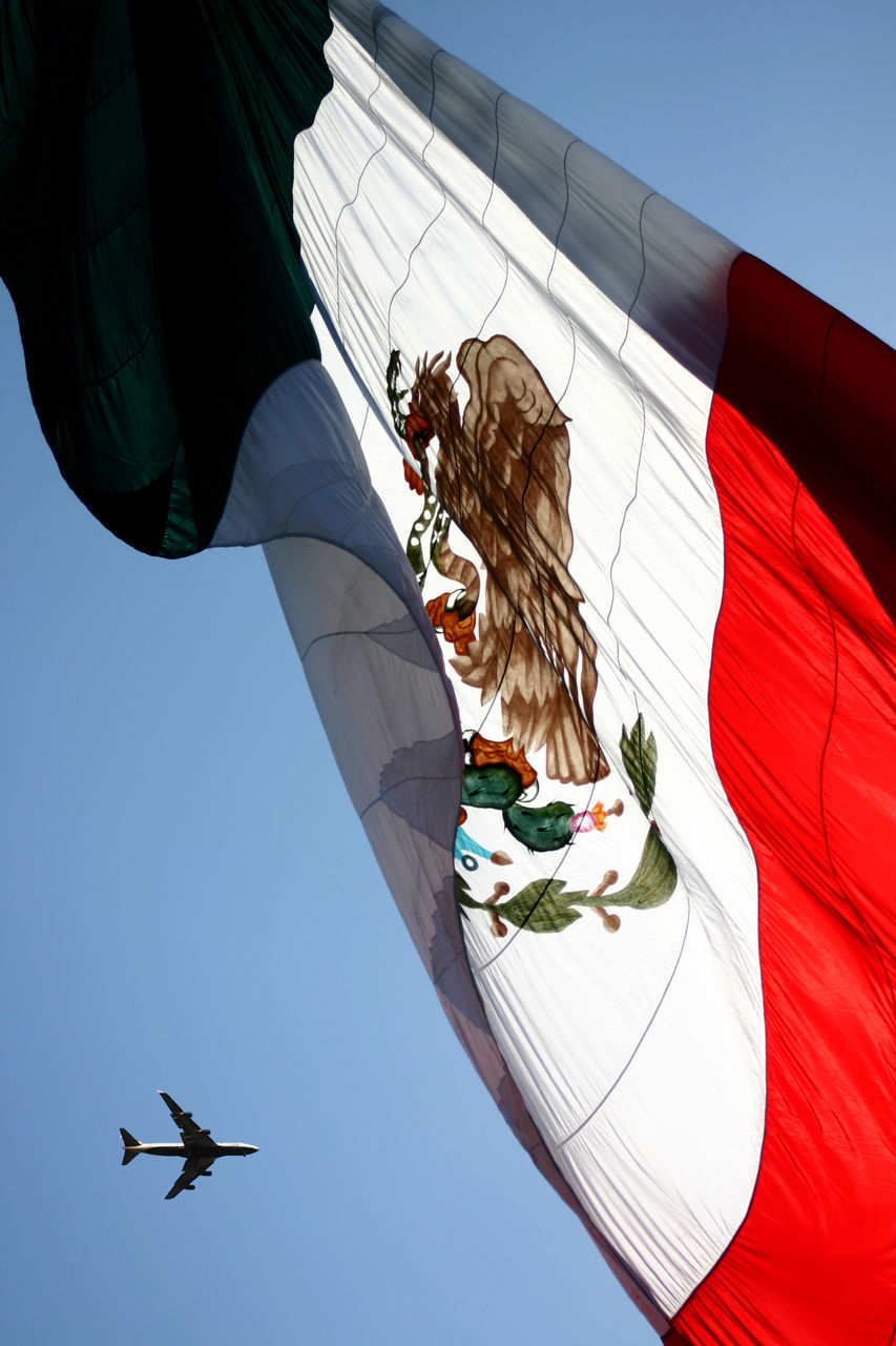 Low Angle View Of Airplane By Mexican Flag Against Sky