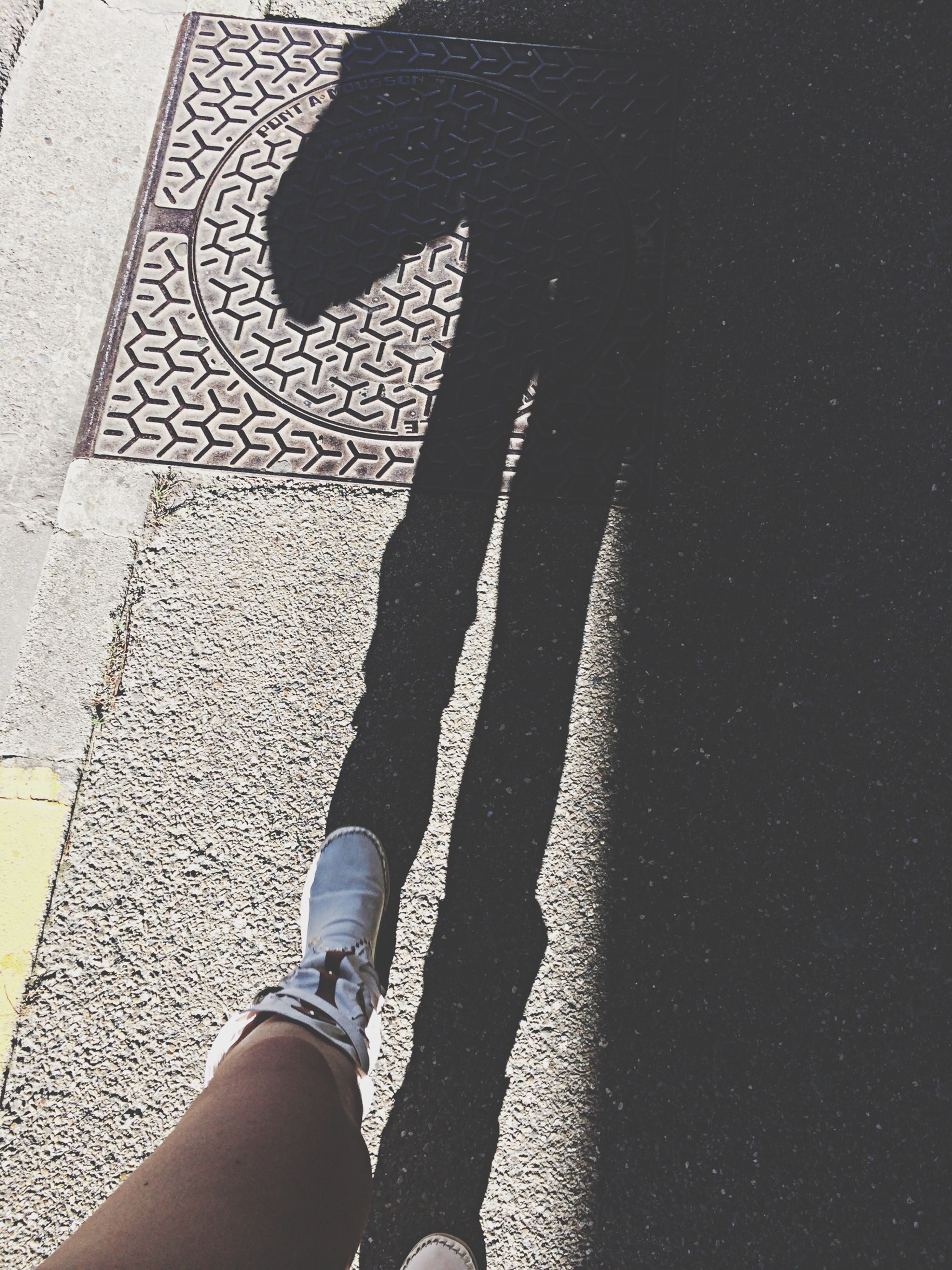 low section, person, lifestyles, leisure activity, high angle view, shoe, shadow, standing, personal perspective, unrecognizable person, men, part of, human foot, sunlight, street, footwear