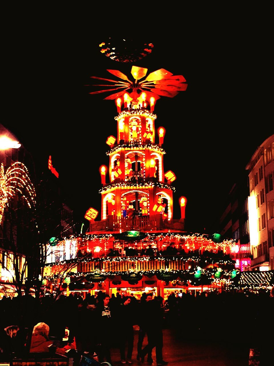 night, illuminated, celebration, large group of people, architecture, built structure, tradition, building exterior, outdoors, christmas decoration, real people, city, low angle view, sky, men, crowd, christmas market, people