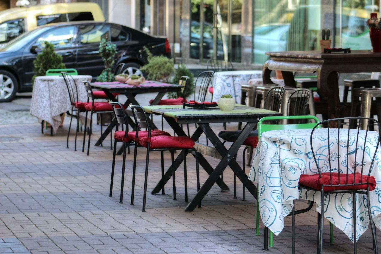 Absence Arrangement Building Exterior Cafe Chair Chairs City Life Empty Focus On Foreground Group Of Objects Outdoors Pink Color Red Restaurant Sidewalk Cafe Street Table Tables Vibrant Color