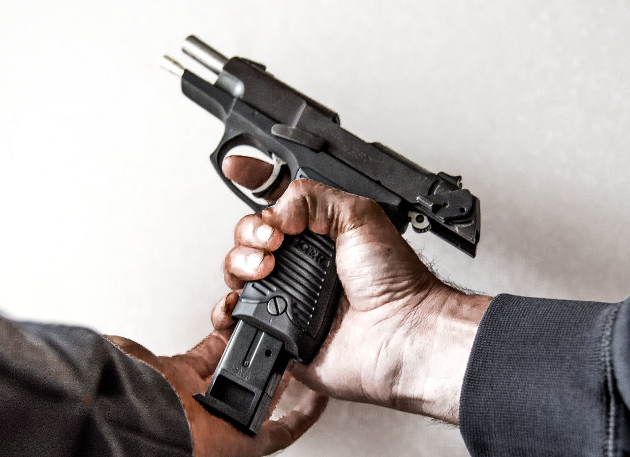 Loading a handgun point of view Adult Aiming Ammunition Close-up Criminal Danger Dirty Gun Guns Handgun Hands Horizontal Human Body Part Law Law Enforcement Men Nra People Pistol Police Self-defense Shooting Theif Weapon White Background