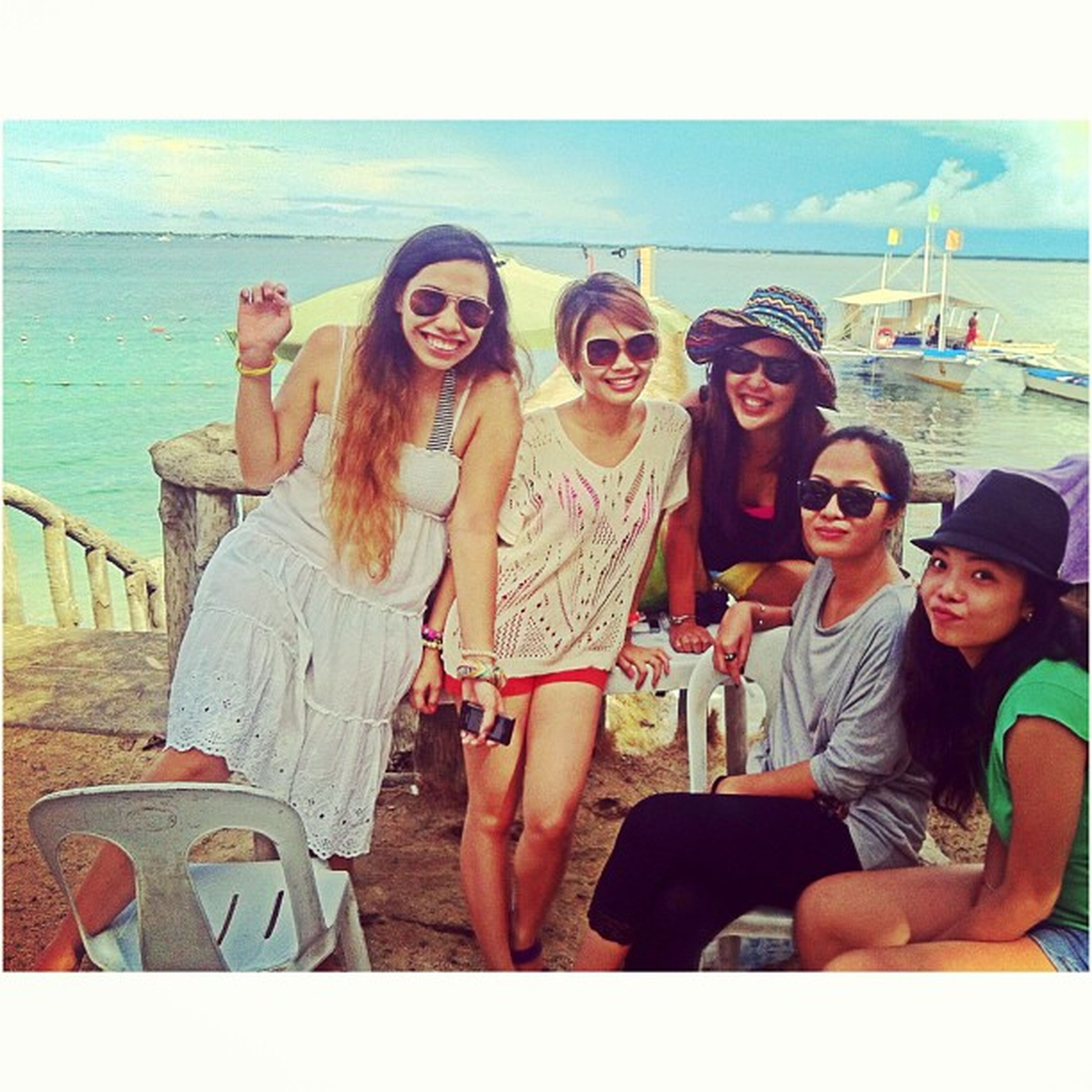 togetherness, person, lifestyles, bonding, leisure activity, love, young adult, sitting, young women, sea, water, beach, smiling, happiness, casual clothing, looking at camera, friendship