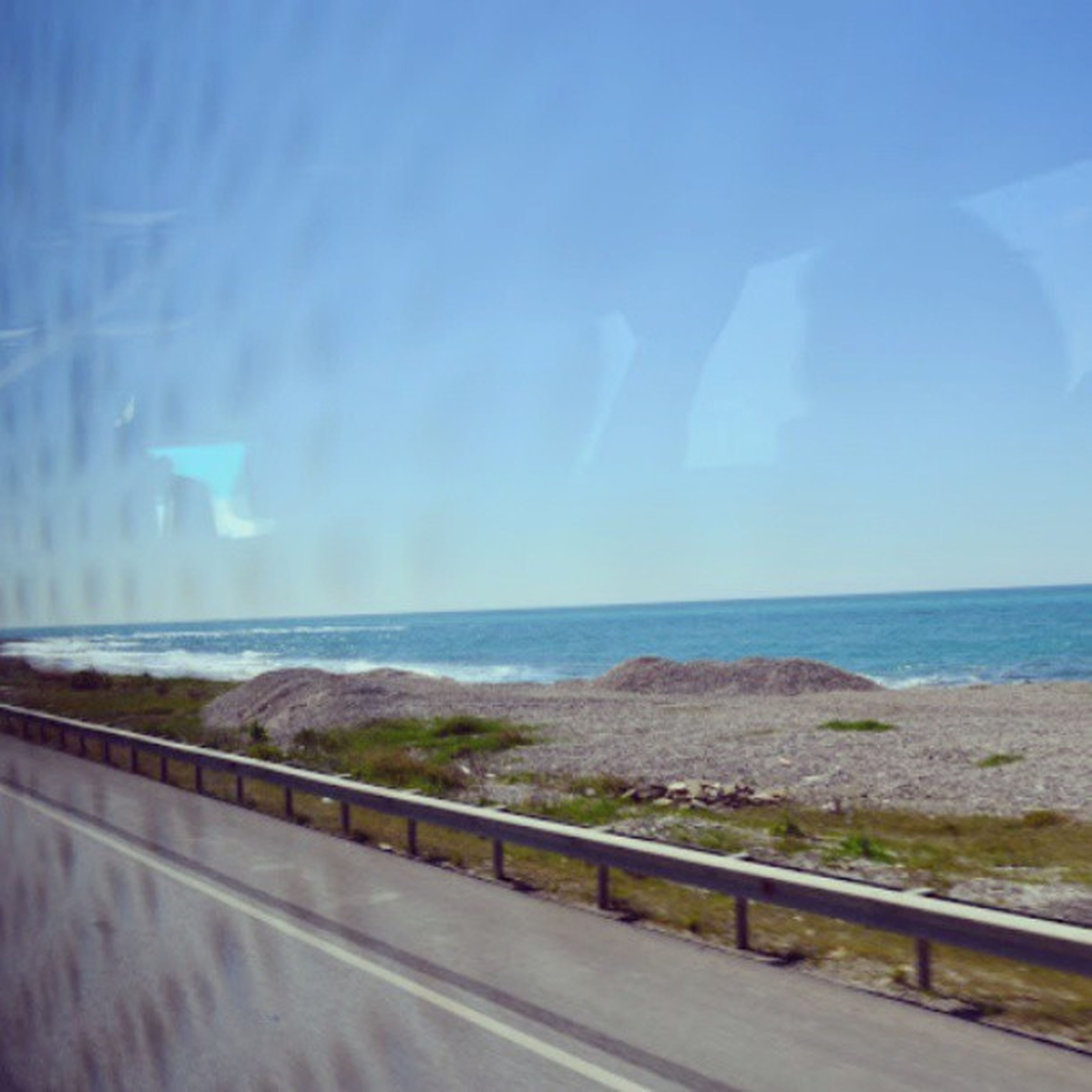water, sea, horizon over water, sky, blue, scenics, beauty in nature, tranquil scene, nature, tranquility, transportation, transparent, road, idyllic, beach, glass - material, day, no people, railing, outdoors