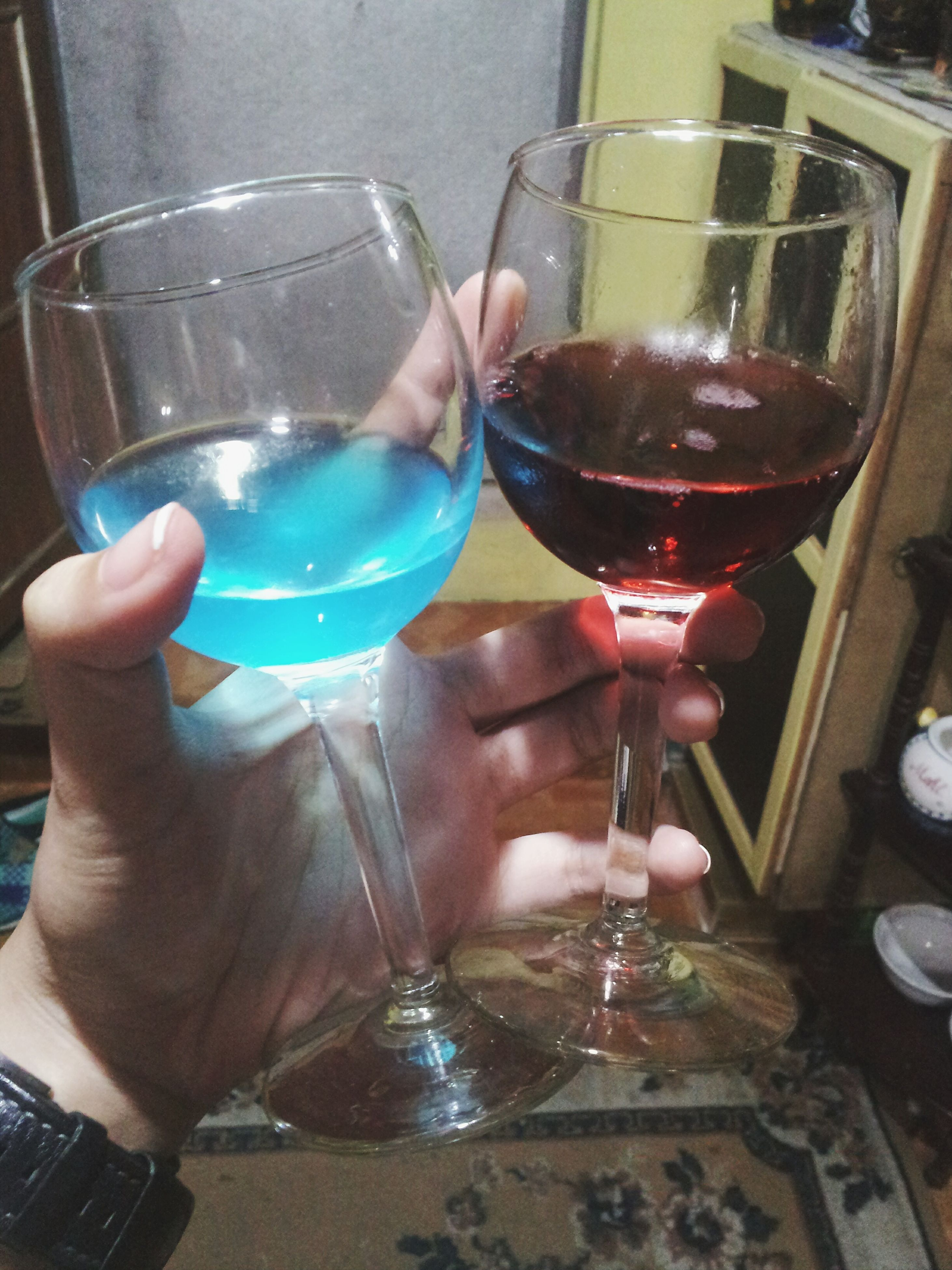 food and drink, drink, person, indoors, refreshment, drinking glass, freshness, holding, table, part of, cropped, lifestyles, glass - material, leisure activity, wineglass, unrecognizable person, human finger