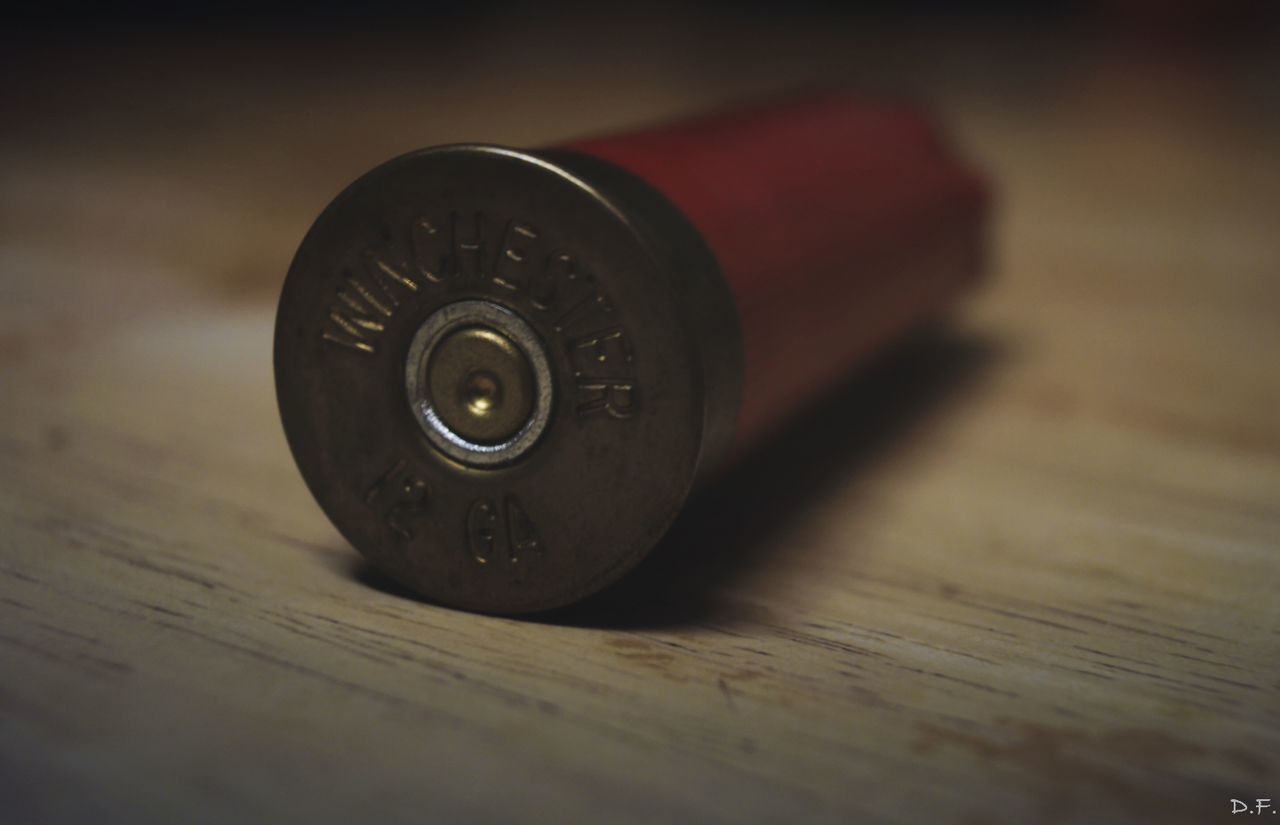 table, no people, indoors, metal, close-up, focus on foreground, wood - material, bullet, day