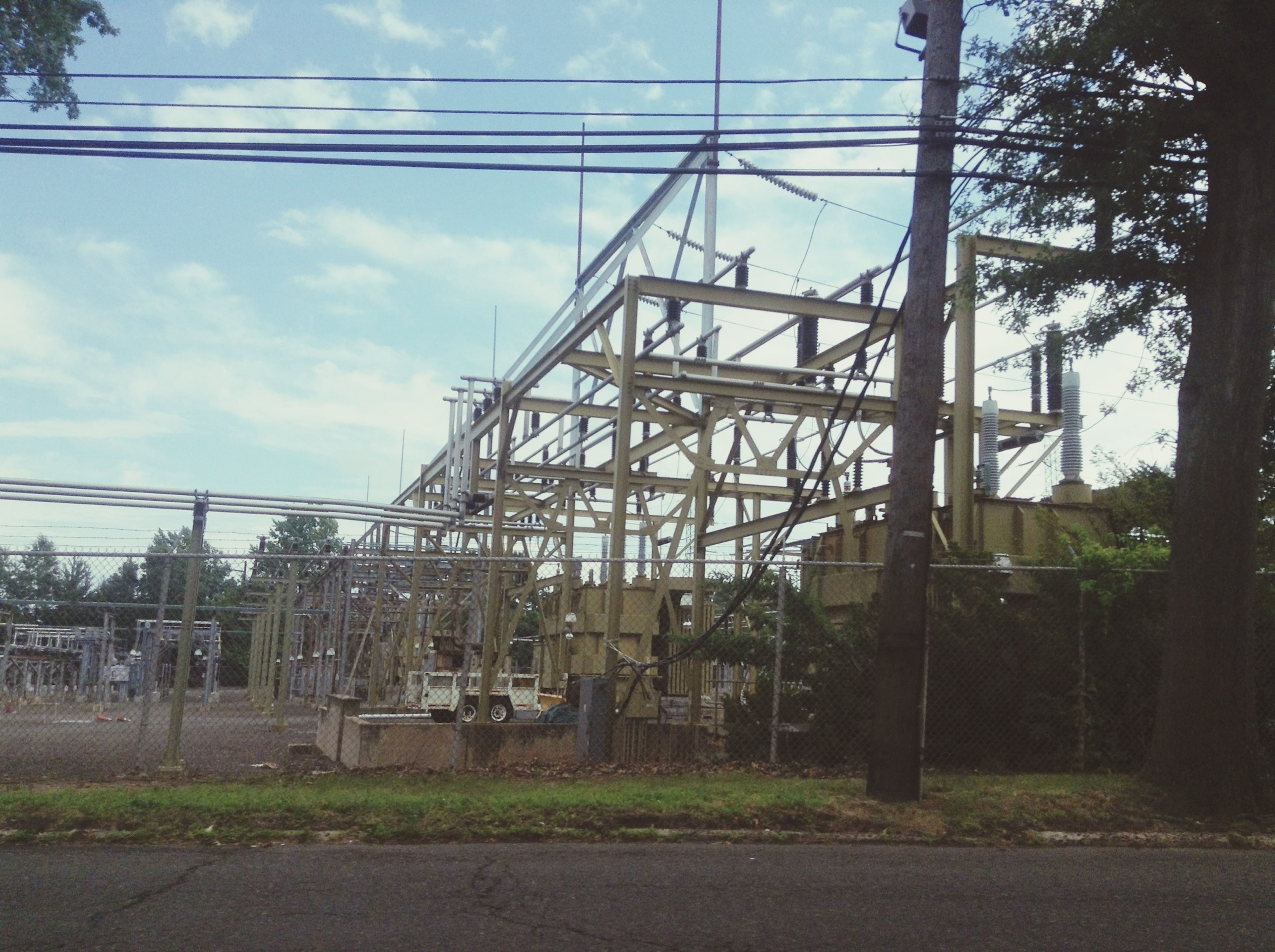 architecture, built structure, building exterior, power line, sky, electricity pylon, power supply, cable, electricity, railroad track, connection, cloud - sky, cloud, day, fuel and power generation, no people, rail transportation, house, low angle view, outdoors