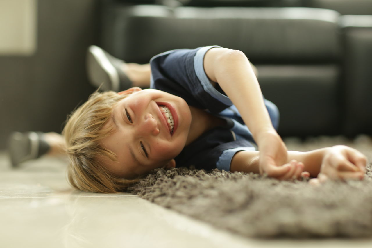 Happy Playful Boy Lying Down On Rug At Home