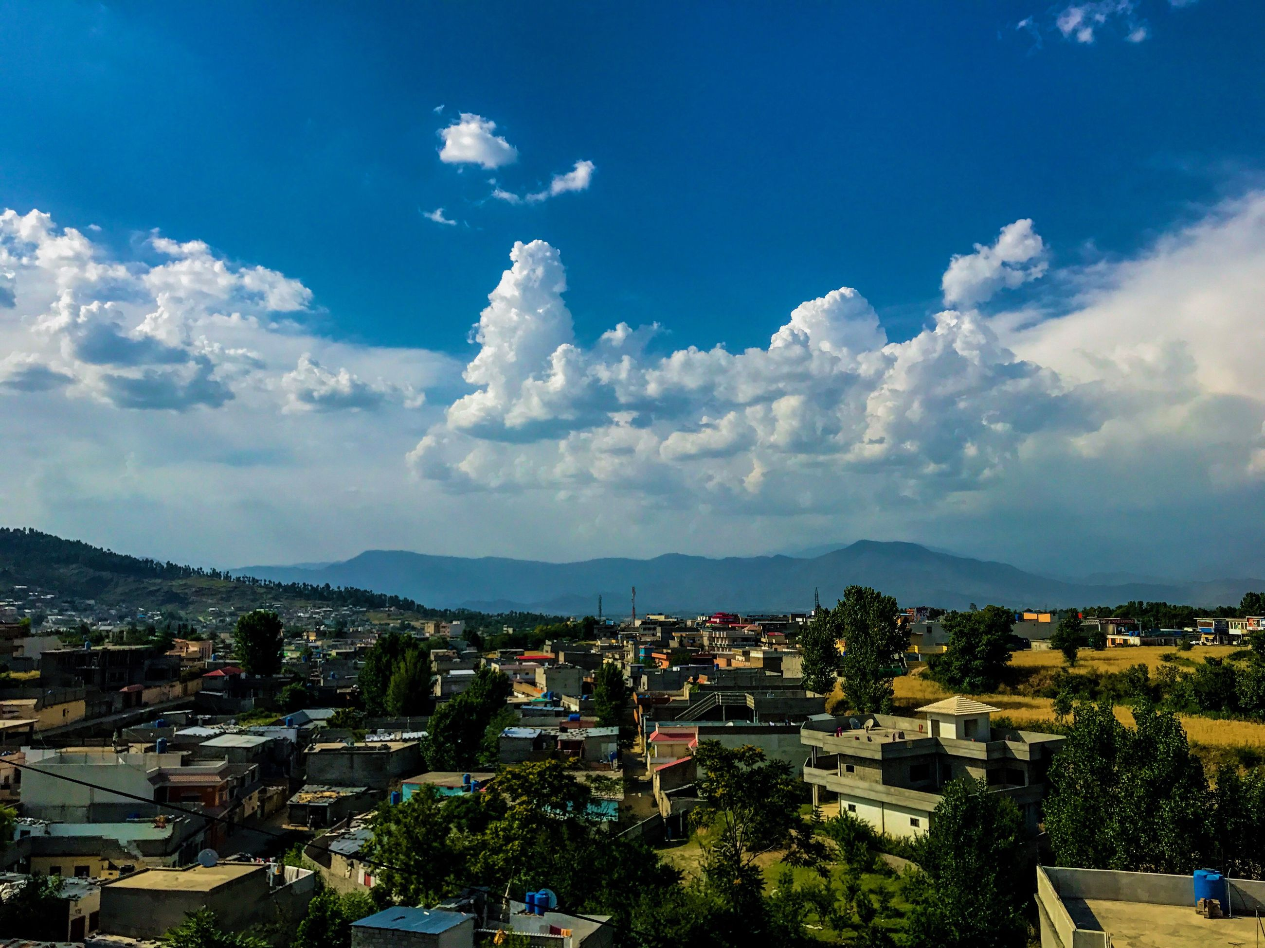 architecture, building exterior, built structure, sky, cloud - sky, high angle view, town, crowded, house, mountain, residential building, outdoors, day, roof, city, cityscape, scenics, community, tree, beauty in nature, nature, residential