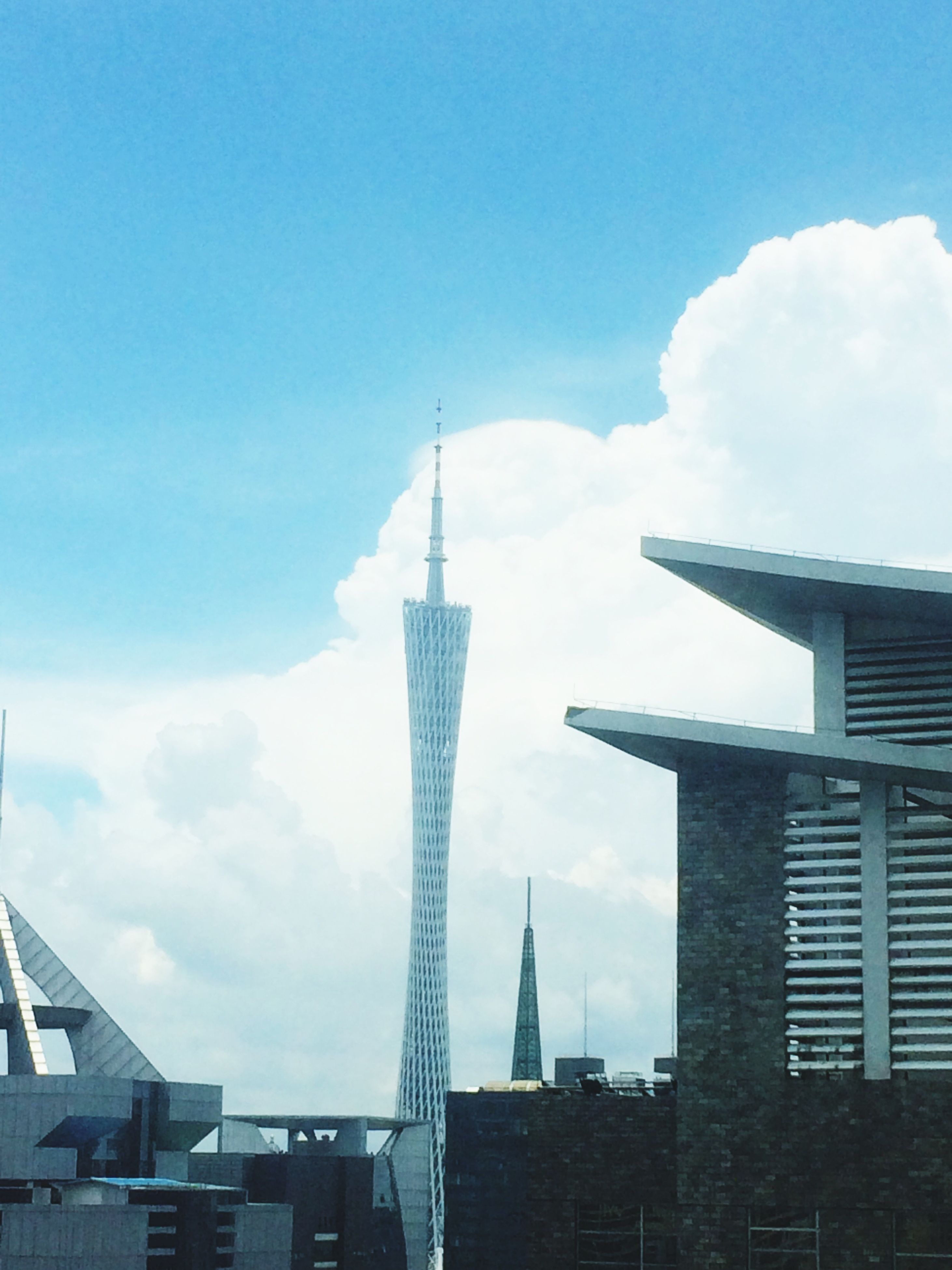 architecture, building exterior, built structure, tall - high, tower, city, skyscraper, low angle view, sky, spire, travel destinations, capital cities, modern, famous place, communications tower, international landmark, cloud - sky, office building, tourism, day