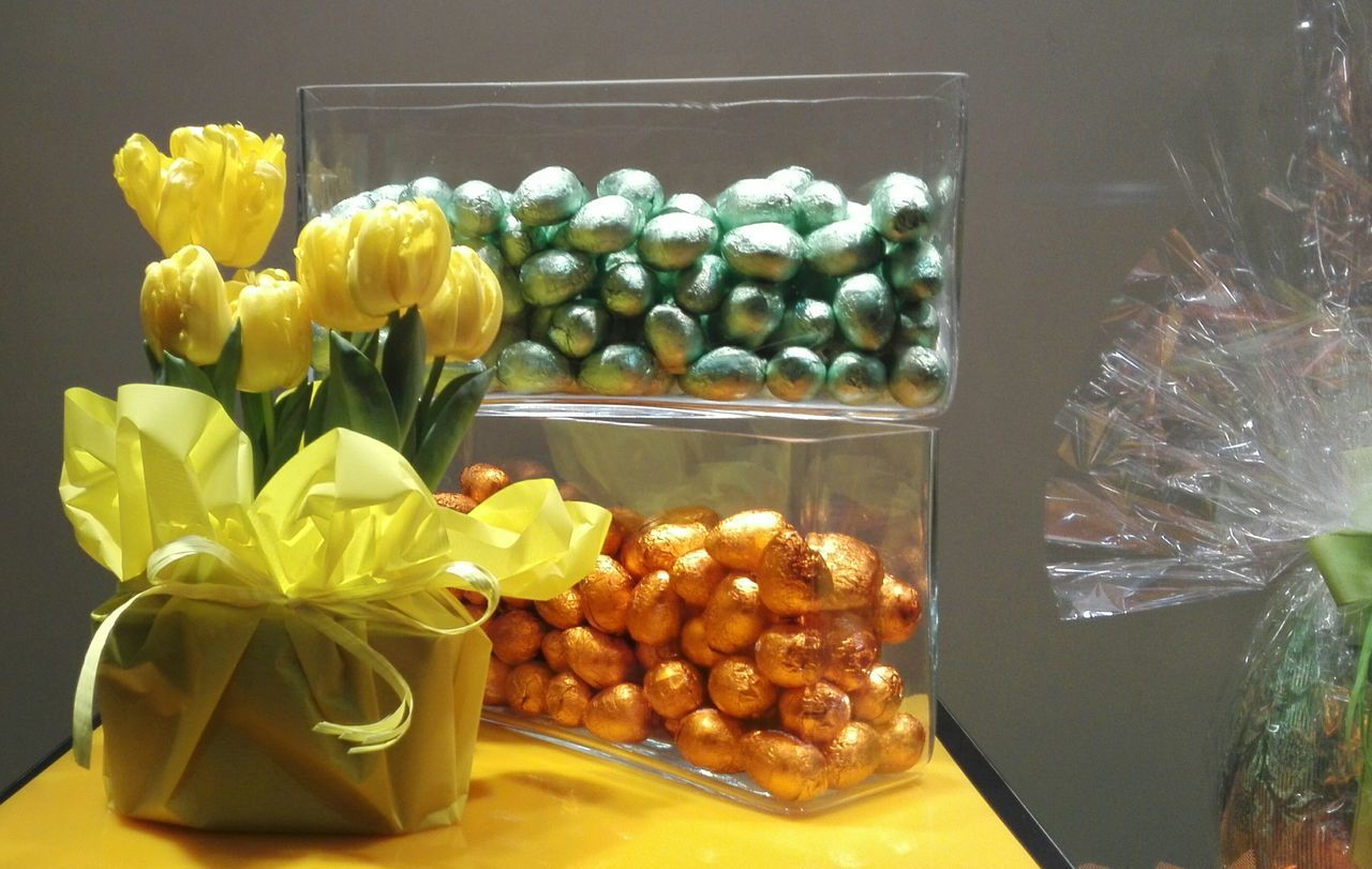 Wrapped Gift Box With Yellow Tulips And Candies On Table