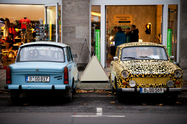 Berlin Cars City City Life Day Eastberlin Germany Information Sign Leopard Print Mode Of Transport Outdoors Park Parking Small Car Store Trabant Trabi Westberlin Two Is Better Than One Battle Of The Cities