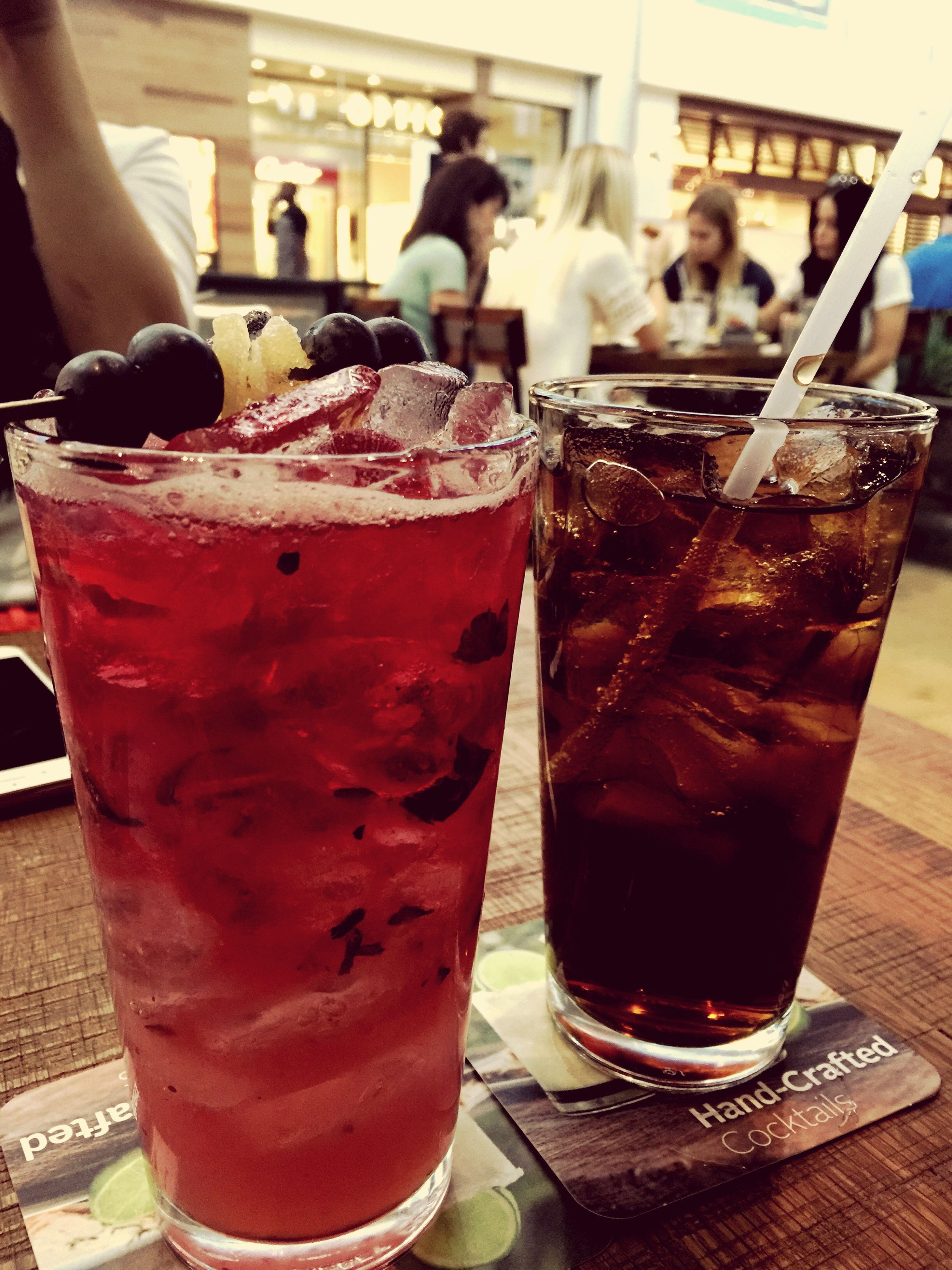 food and drink, drink, refreshment, drinking glass, freshness, table, indoors, alcohol, restaurant, close-up, glass - material, still life, juice, focus on foreground, drinking straw, glass, cocktail, incidental people, beer glass, ice cube