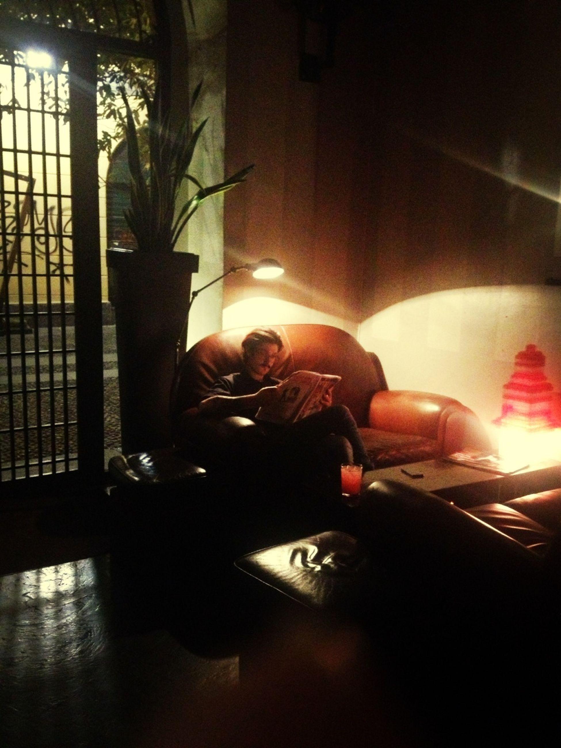 indoors, illuminated, night, home interior, lighting equipment, light - natural phenomenon, dark, glowing, sitting, sunlight, reflection, table, lifestyles, chair, house, domestic room, men, high angle view