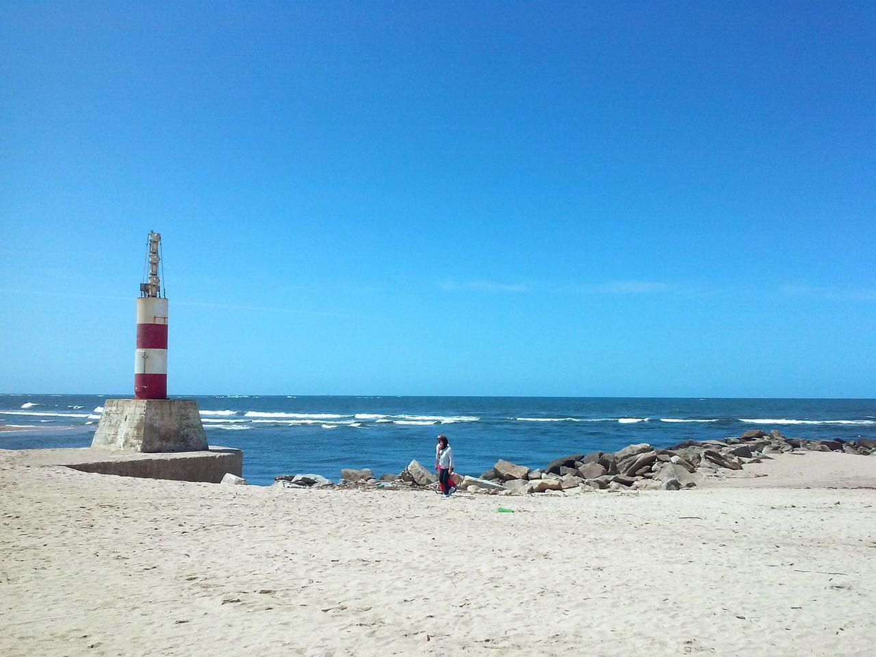sea, horizon over water, beach, water, nature, lighthouse, scenics, sand, day, copy space, tranquility, clear sky, beauty in nature, blue, tranquil scene, built structure, sky, architecture, real people, outdoors, building exterior, men, one person, people