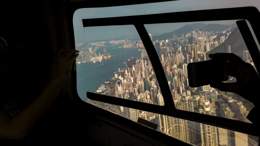 Buildings And Sky Buildings From Above Cityscape Flying In Flying In China Flying In The Sky Helicopter Hong Kong Helicopter Ride Helicopter View Hong Kon High Contrast Image Holding In Hand Hong Kong Buildings Hong Kong City Hong Kong Harbour Iphone In Image Kowloon Bay Kowloon Helicopter Ride Kowloon, HK Looking Through Window Mode Of Transport Sillhoette Iphone Silouette Photography Skyline Hong Kong View Hong Kong Window