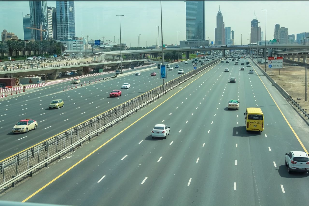 car, transportation, traffic, city, road, on the move, mode of transport, land vehicle, highway, speed, architecture, high angle view, city life, street, motion, city street, built structure, building exterior, outdoors, travel, rush hour, skyscraper, downtown district, day, travel destinations, no people, cityscape, sky