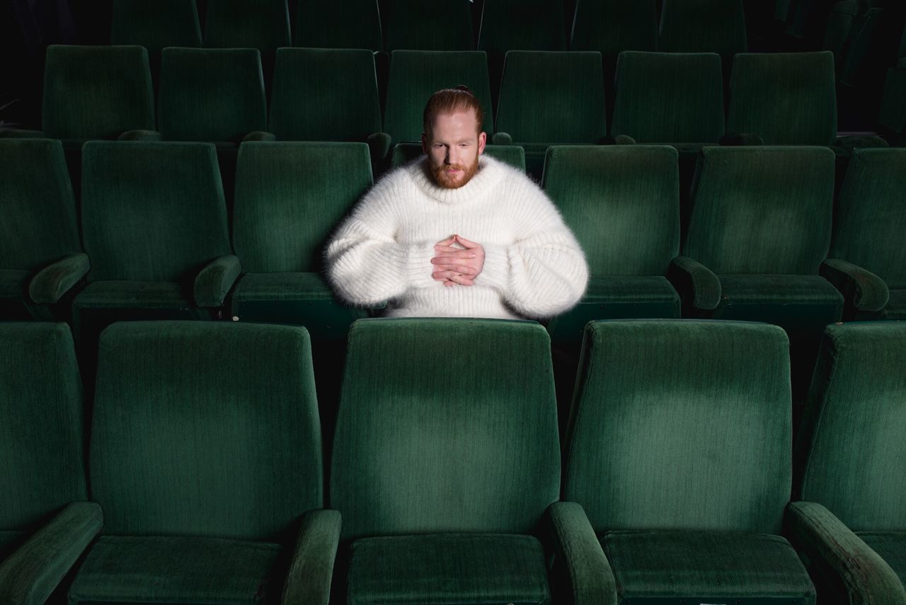 one man only, front view, one person, sofa, males, only men, beard, adults only, green color, stage theater, adult, people, indoors, fan - enthusiast, auditorium, couch potato