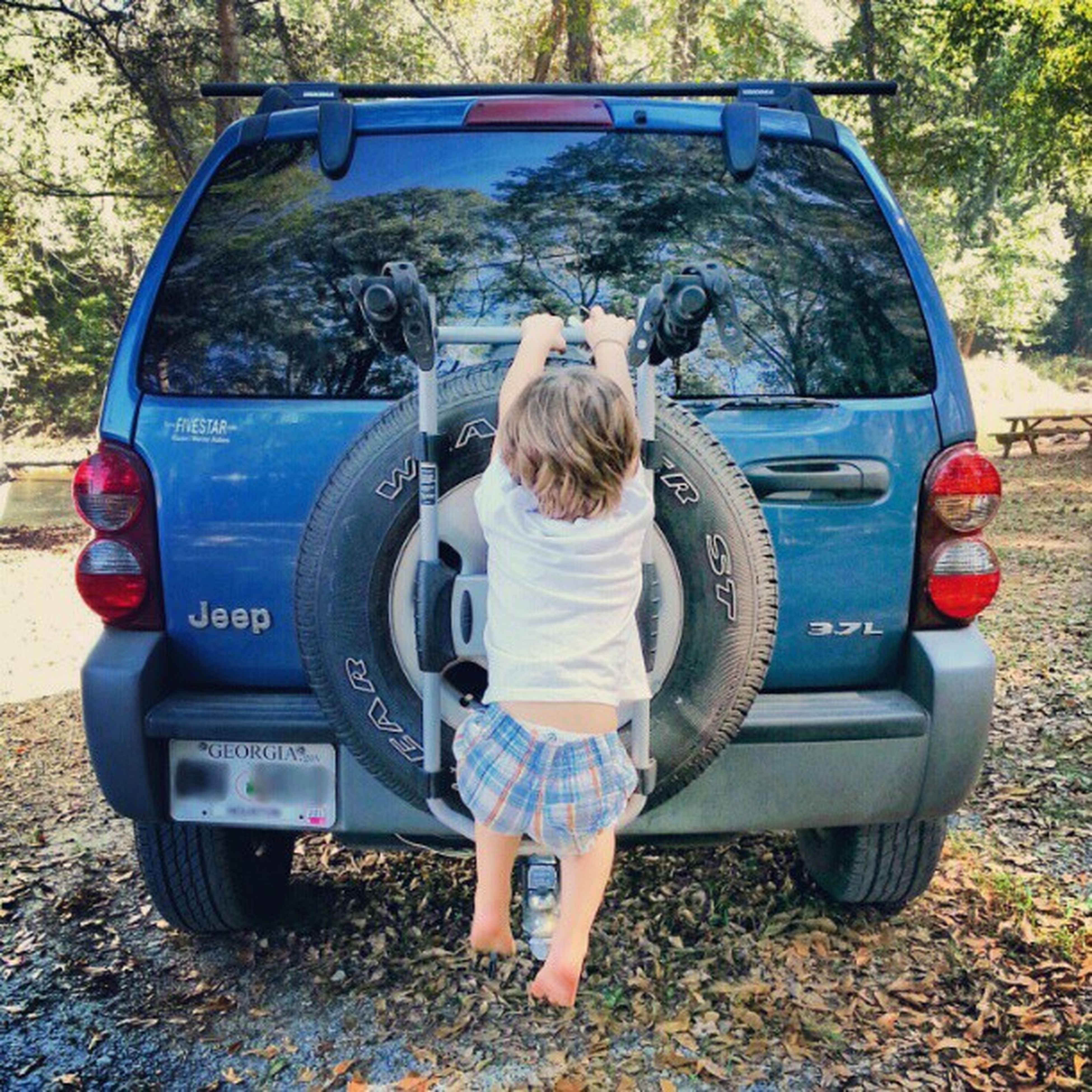 childhood, full length, elementary age, sitting, casual clothing, land vehicle, lifestyles, high angle view, car, transportation, day, leisure activity, rear view, toy, girls, innocence, cute, boys