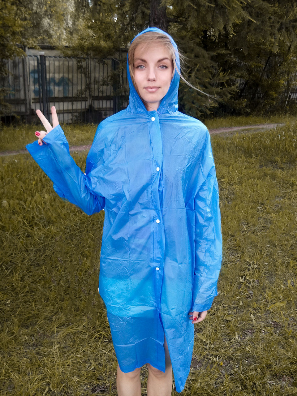 Portrait Of Woman Wearing Blue Raincoat Gesturing Peace Sign While Standing On Grassy Field At Yard