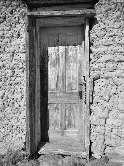"""""""Mystery Ranch No. 22"""" Where once it opened on life. Mystery New Mexico Photography New Mexico Abandoned Buildings Abandoned Places Abandoned Adobe Weathered Doors Black And White Photography Black And White Blackandwhite Door Architecture Built Structure Day No People Building Exterior Outdoors"""
