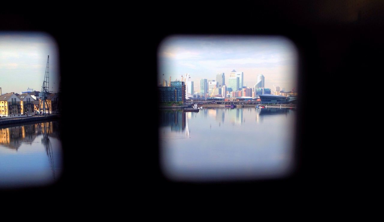Peeking through Through The Gap Spy Spying Spyhole Hole In The Wall Docks London City Across The Water In The Distance