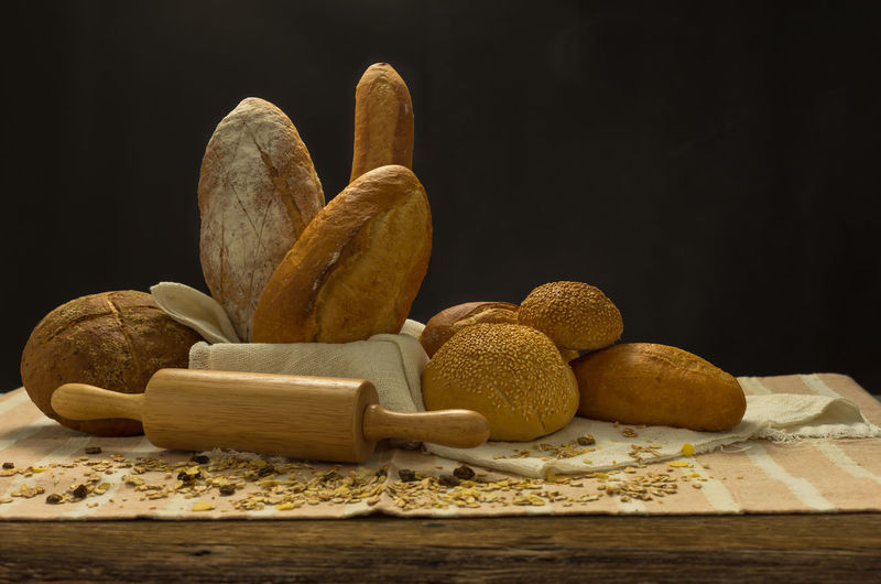 Still life with breads on the table with black background. Wood - Material Food Close-up Studio Shot Breads Still Life Food