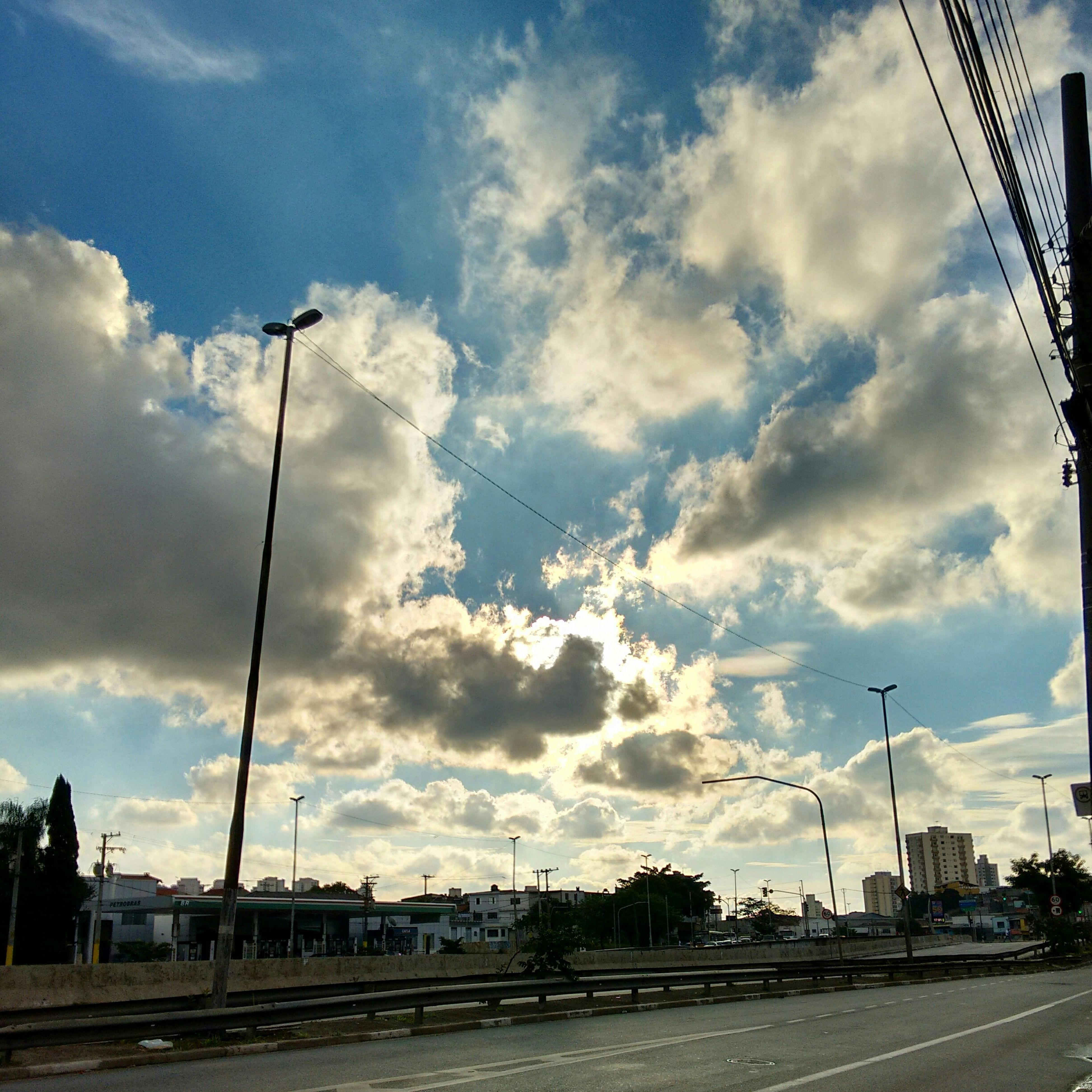 sky, transportation, power line, street light, electricity pylon, cloud - sky, road, the way forward, electricity, built structure, building exterior, cable, connection, power supply, street, cloudy, architecture, cloud, car, diminishing perspective