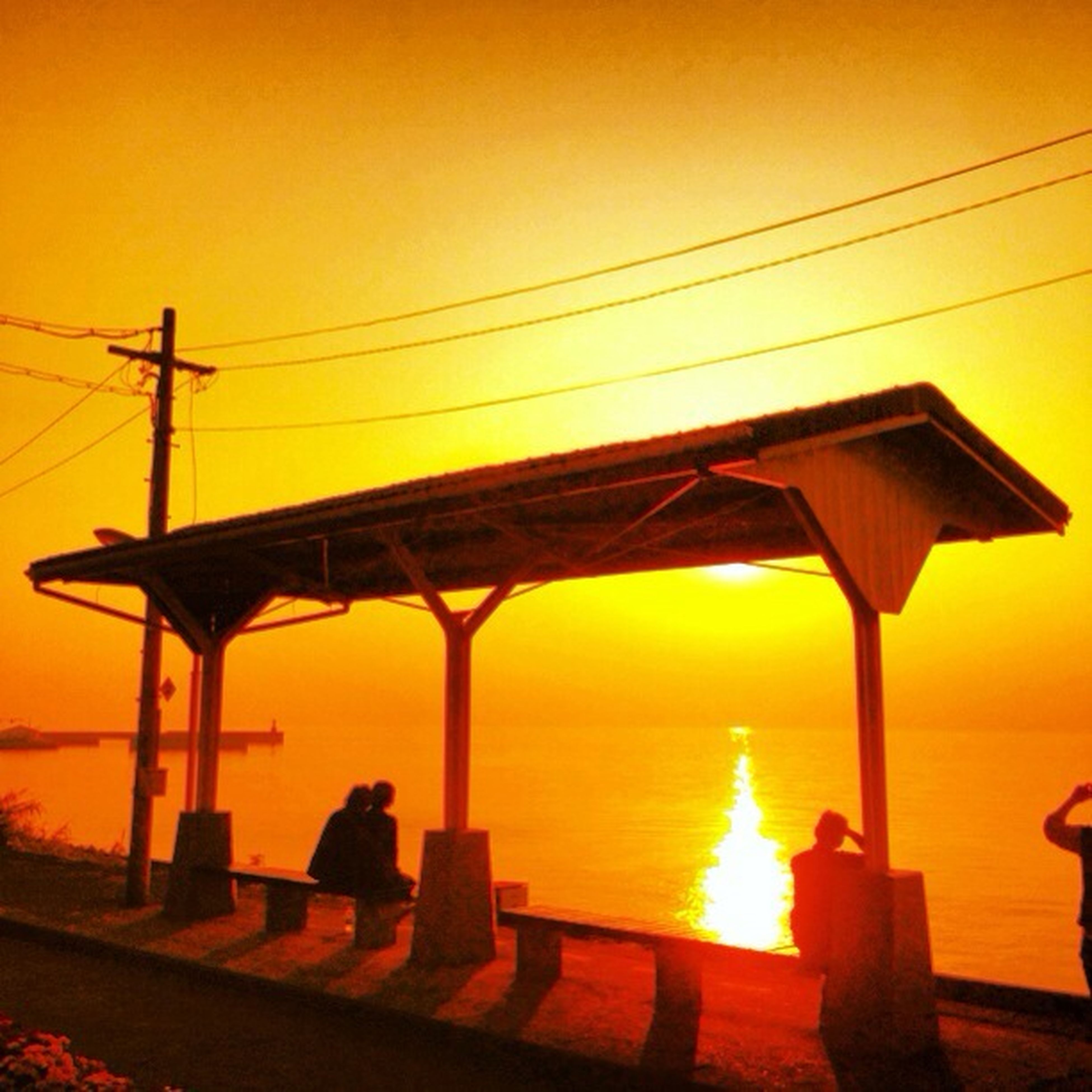 sunset, water, connection, orange color, transportation, built structure, sea, railing, sky, sunlight, street light, nature, sun, power line, no people, yellow, outdoors, electricity, tranquility, beauty in nature