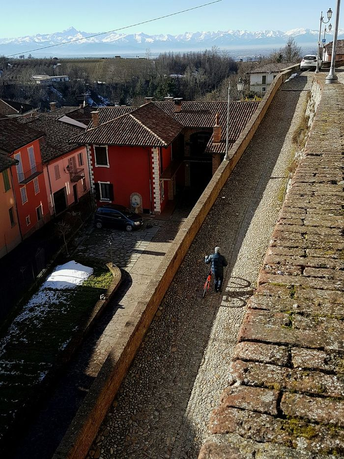 Architecture Built Structure Building Exterior High Angle View Outdoors City Sky Day Travel Destinations On The Street Tranquility Airy Piedmont Italy Langhe Streets View From The Top Bicycle Bicyclist Real People Cold Temperature Calming Views Winter Landscape At The Top Of The Hill