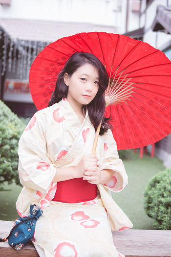 Beautiful Woman Day Front View Happiness Holding Kimono Leisure Activity Lifestyles Looking At Camera One Person Outdoors Portrait Real People Red Smiling Standing Three Quarter Length Traditional Clothing Young Adult Young Women