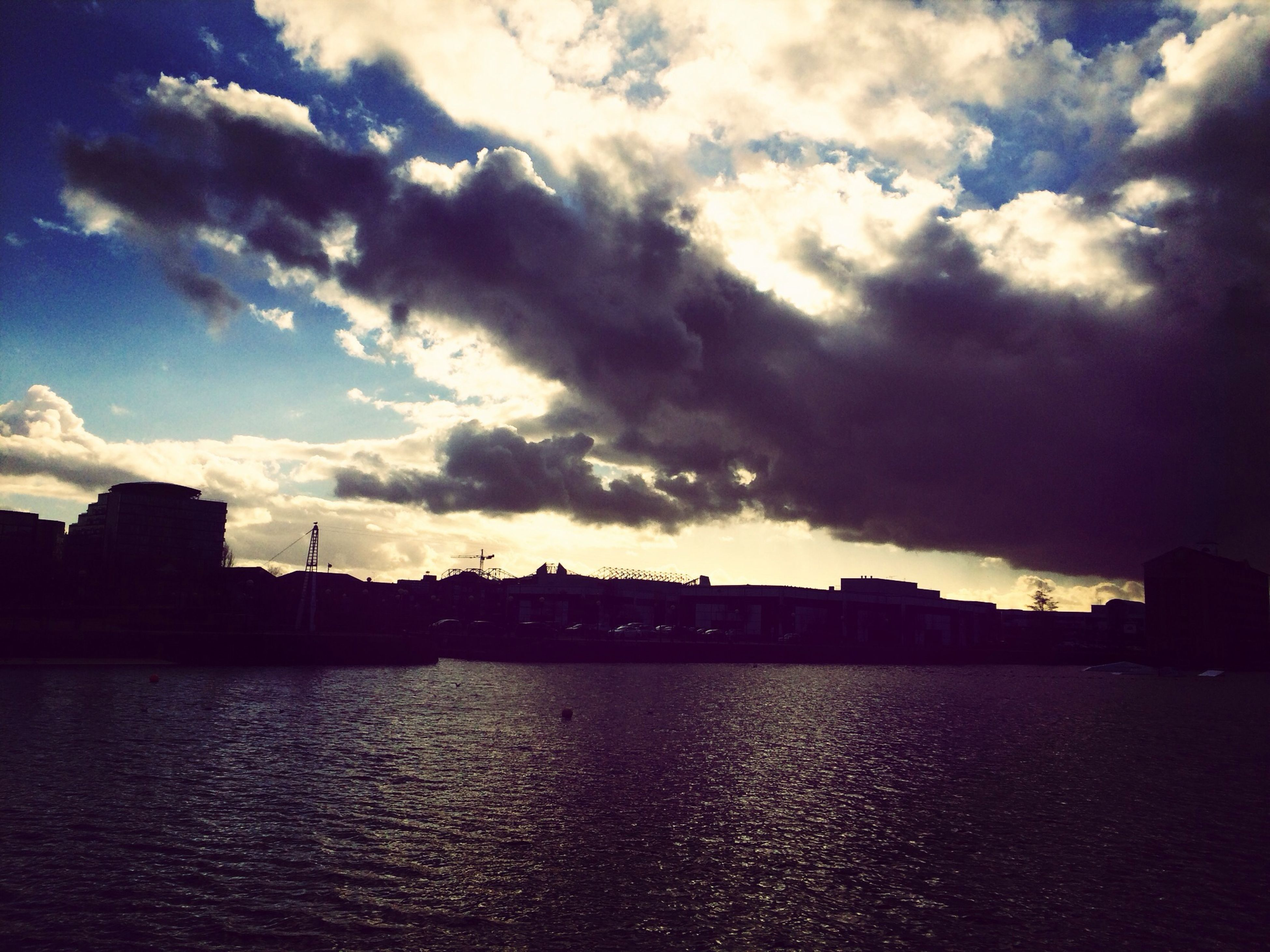 architecture, sky, building exterior, built structure, cloud - sky, silhouette, waterfront, water, sunset, cloudy, cloud, city, river, dusk, nature, scenics, building, weather, outdoors, residential building
